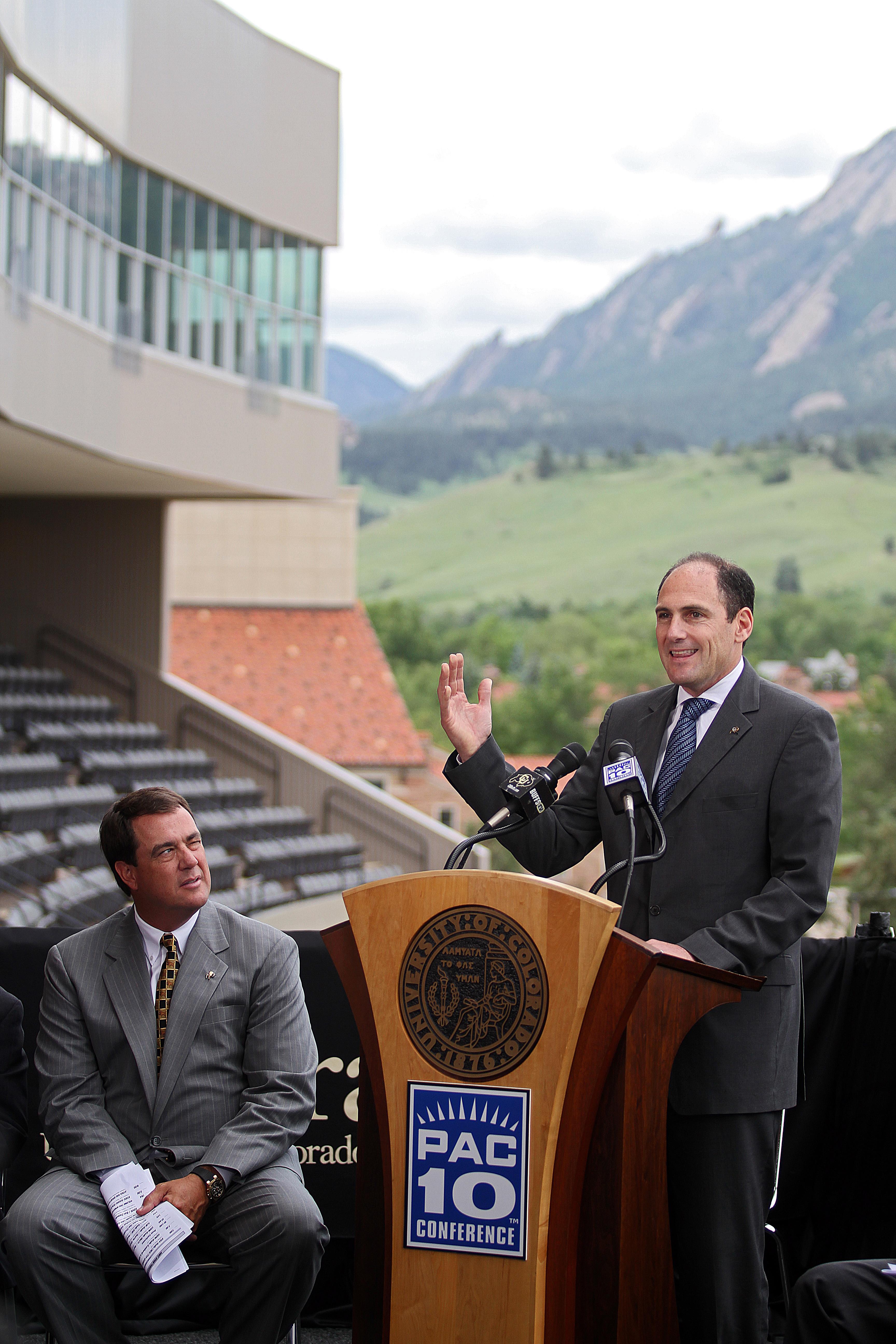 BOULDER, CO - JUNE 11:  University of Colorado Athletic Director Mike Bohn (L) listens as  PAC-10 Commissioner Larry Scott speaks during a press conference at Folsom Stadium on June 11, 2010 in Boulder, Colorado. The University of Colorado Board of Regent