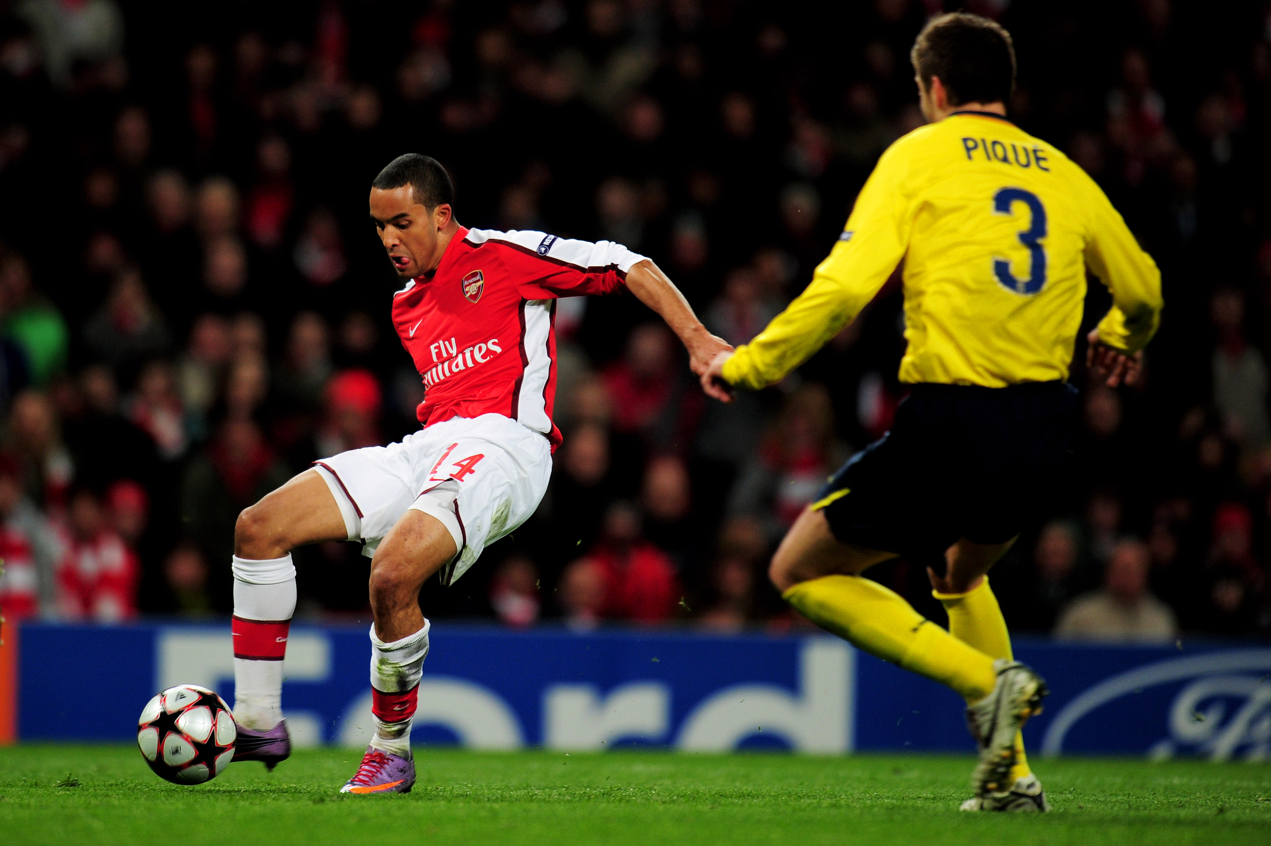LONDON, ENGLAND - MARCH 31:  Theo Walcott of Arsenal shoots past Gerard Pique of Barcelona to score a goal during the UEFA Champions League quarter final first leg match between Arsenal and FC Barcelona at the Emirates Stadium on March 31, 2010 in London,