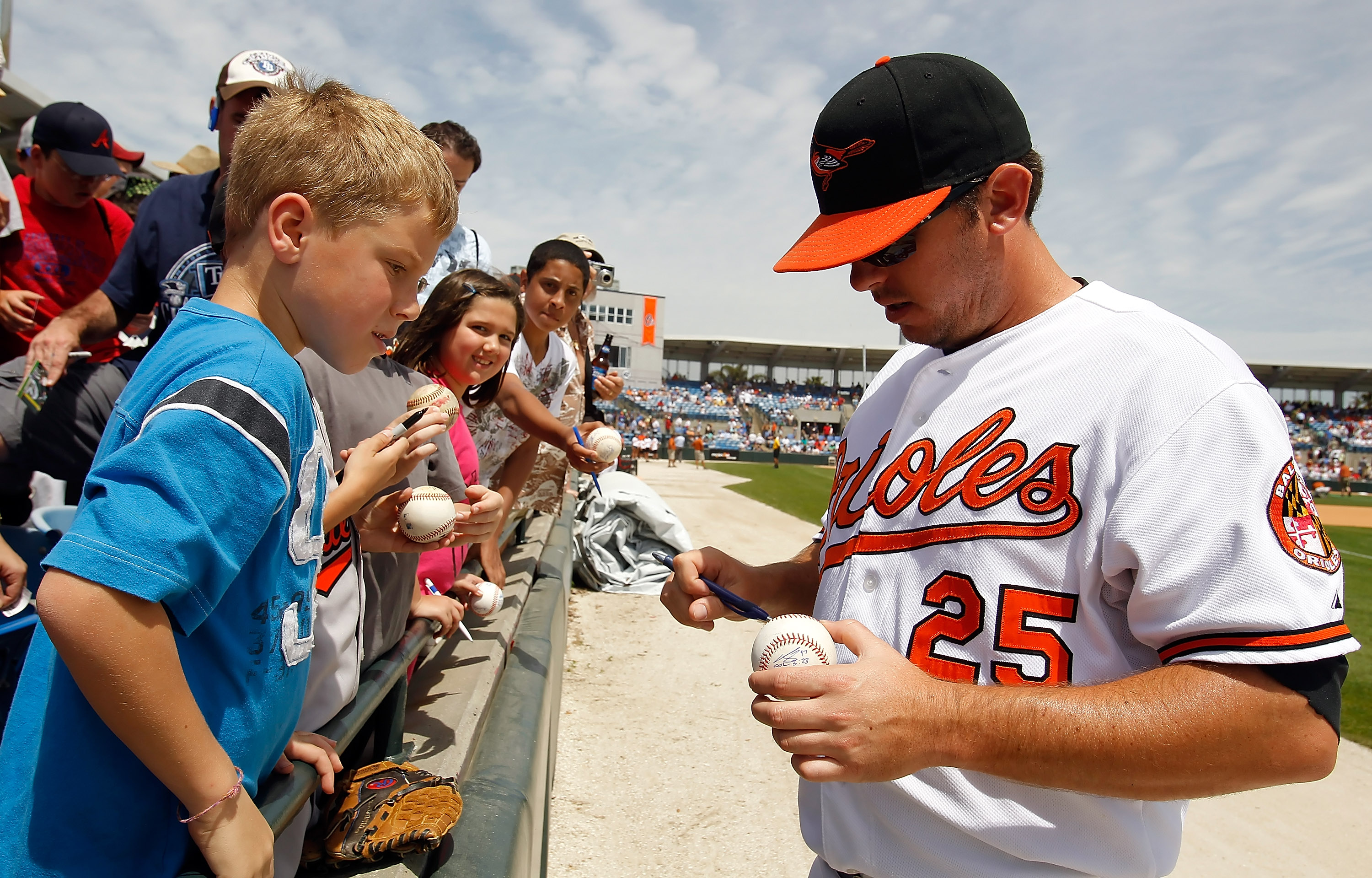 SARASOTA, FL - APRIL 03:  Infielder Garrett Atkins #25 of the Baltimore Orioles signs autographs prior to the start of the Grapefruit League Spring Training Game against the New York Mets at Ed Smith Stadium on April 3, 2010 in Sarasota, Florida.  (Photo