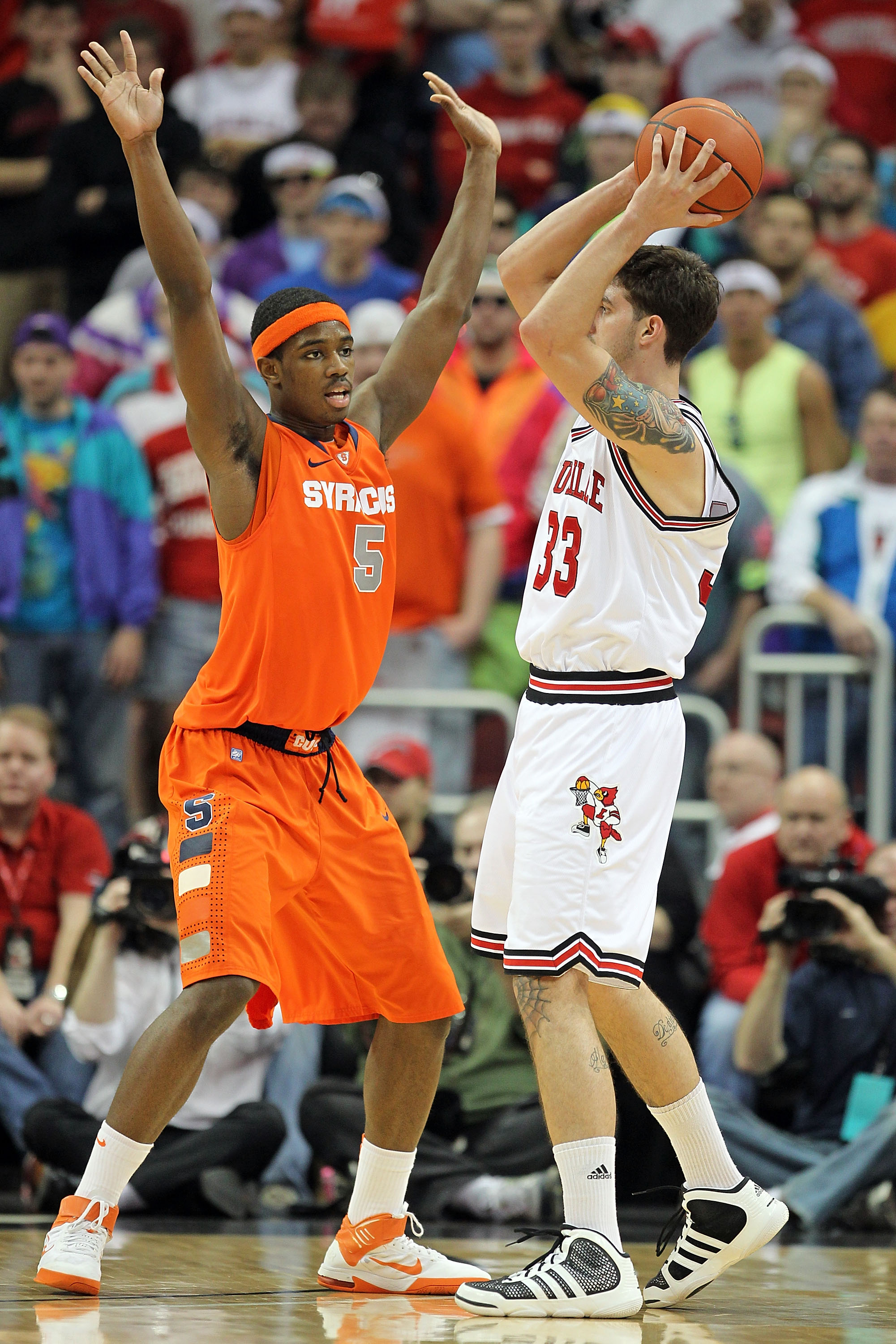 LOUISVILLE, KY - FEBRUARY 12: C.J. Fair #5 of the Syracuse Orange defends Mike Marra #33 of the Louisville Cardinals during the Big East Conference game at the KFC Yum! Center on February 12, 2011 in Louisville, Kentucky.  Louisville won 73-69.  (Photo by