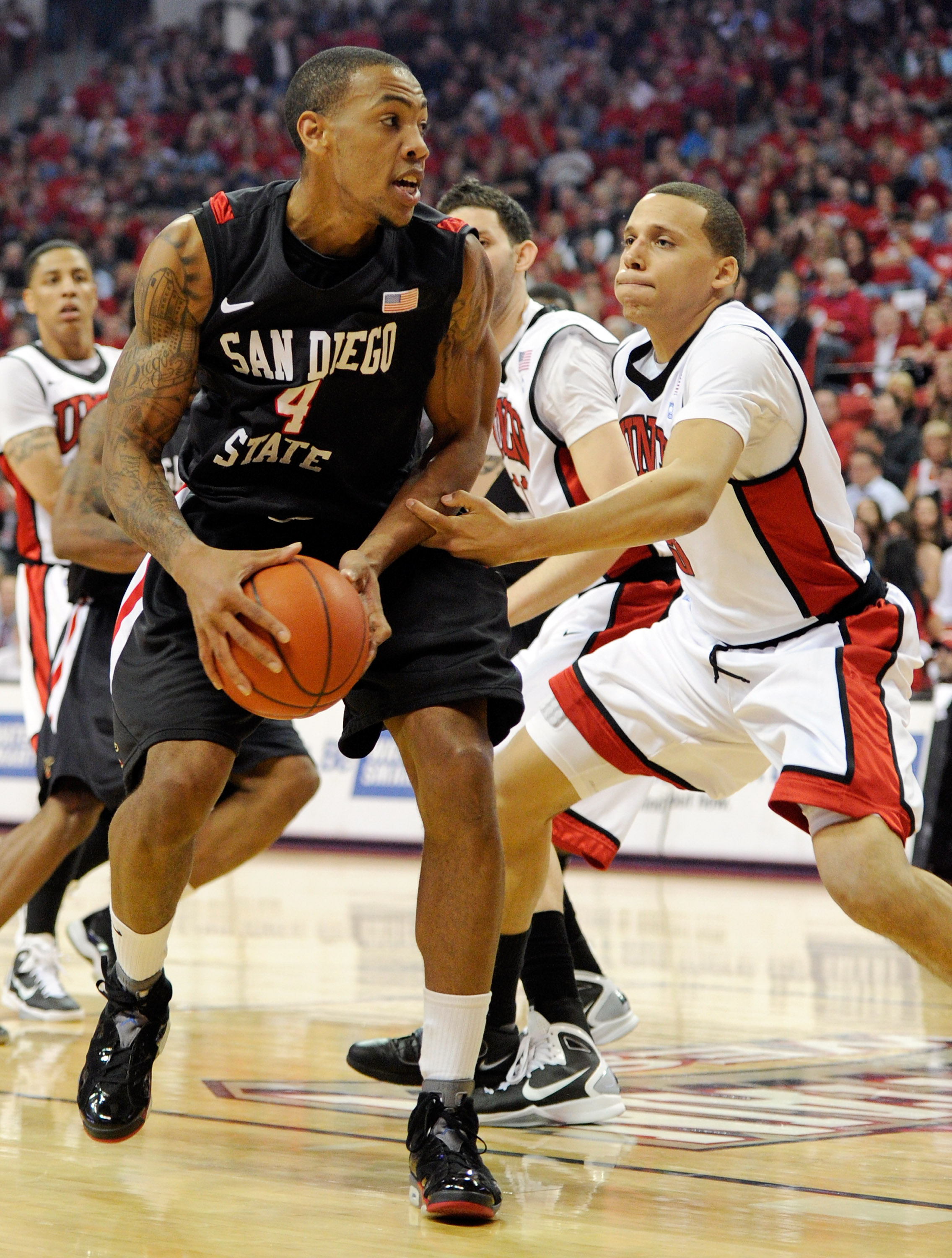 LAS VEGAS, NV - FEBRUARY 12:  Malcolm Thomas #4 of the San Diego State Aztecs goes to the basket against Chace Stanback #22 of the UNLV Rebels during their game at the Thomas & Mack Center February 12, 2011 in Las Vegas, Nevada. San Diego State won 63-57.