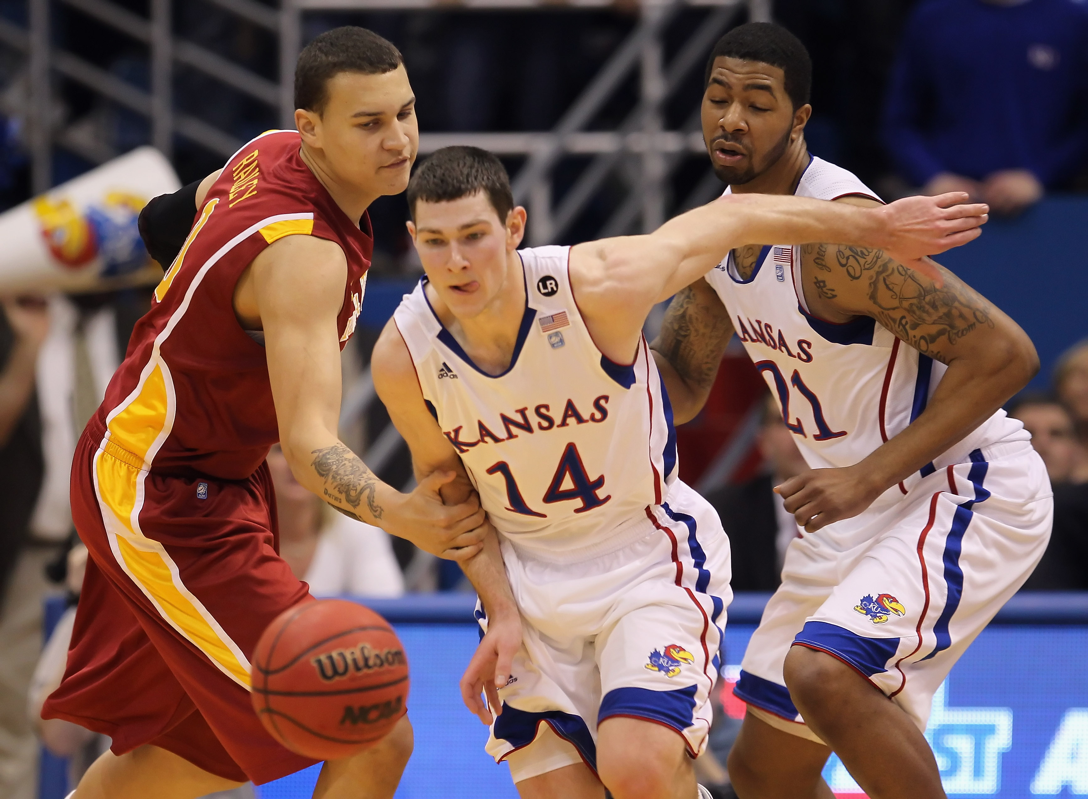LAWRENCE, KS - FEBRUARY 12:  Jordan Railey #0 of the Iowa State Cyclones fouls Tyrel Reed #14 of the Kansas Jayhawks on a loose ball as Markieff Morris #21 looks on during the game on February 12, 2011 at Allen Fieldhouse in Lawrence, Kansas.  (Photo by J