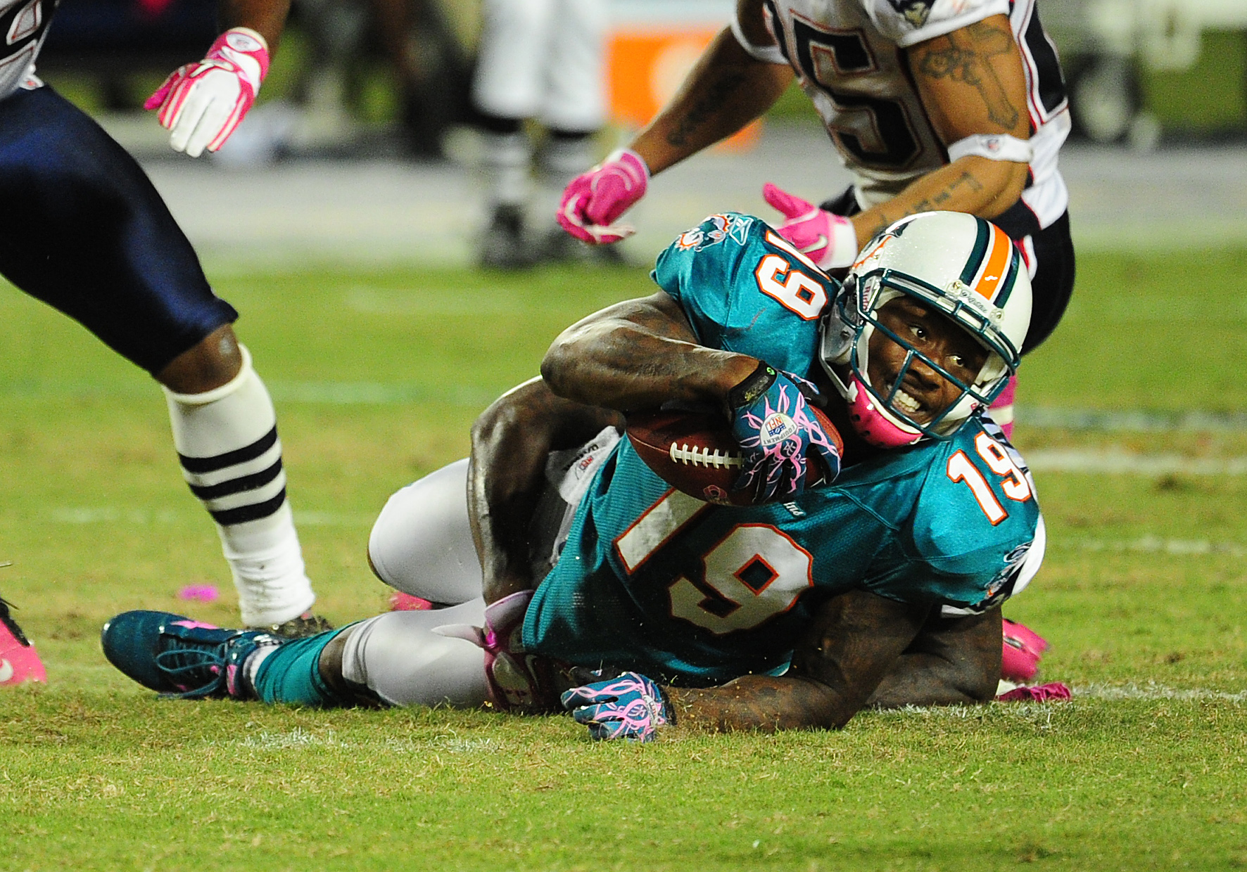 MIAMI - OCTOBER 4: Brandon Marshall #19 of the Miami Dolphins is tackled by Kyle Arrington #27 of the New England Patriots at Sun Life Field on October 4, 2010 in Miami, Florida. (Photo by Scott Cunningham/Getty Images)