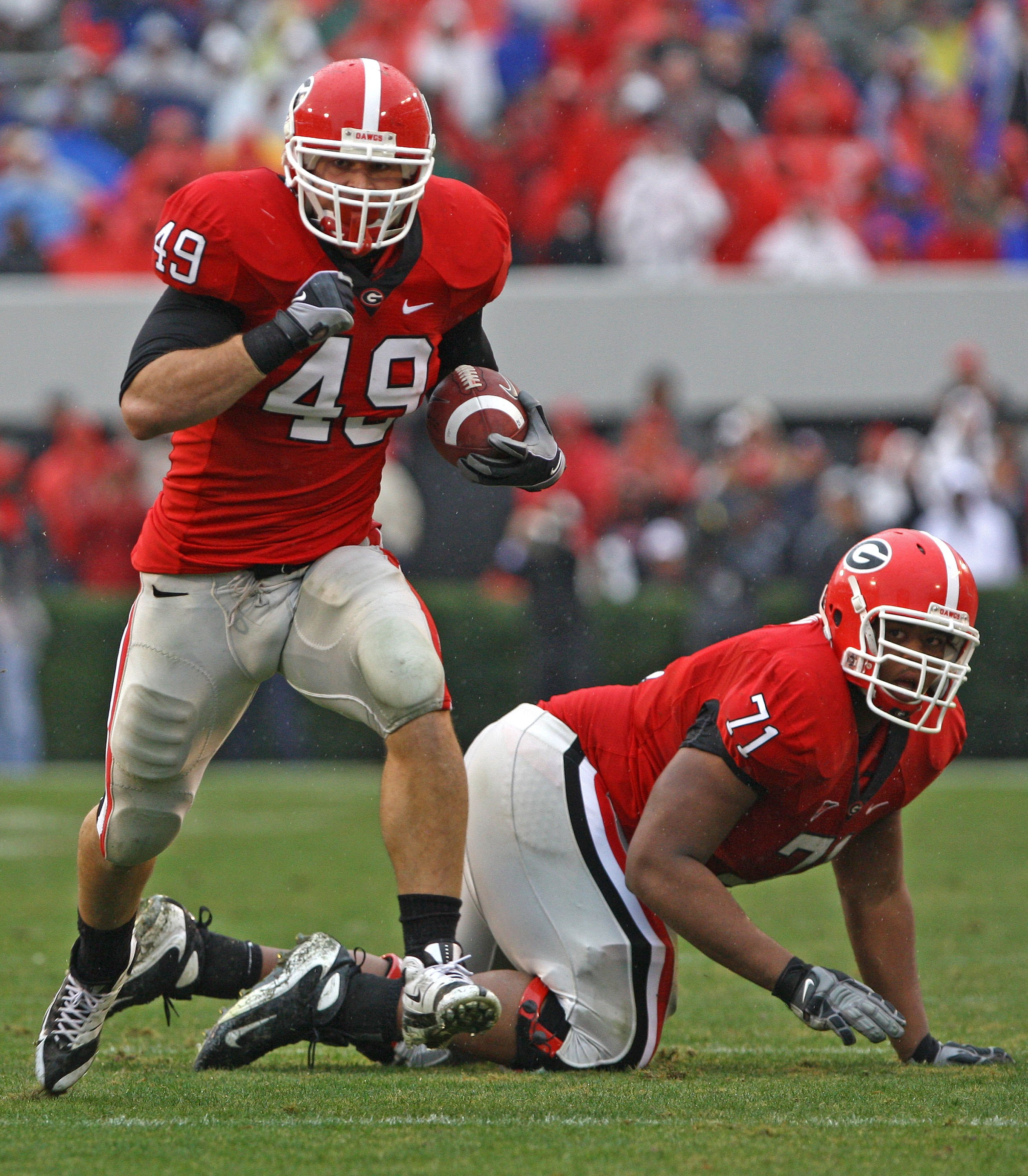 ATHENS, GA - NOVEMBER 29:  Fullback Shaun Chapas #49 of the Georgia Bulldogs runs upfield as teammate and offensive lineman Cordy Glenn watches during the game against the Georgia Tech Yellow Jackets at Sanford Stadium on November 29, 2008 in Athens, Geor