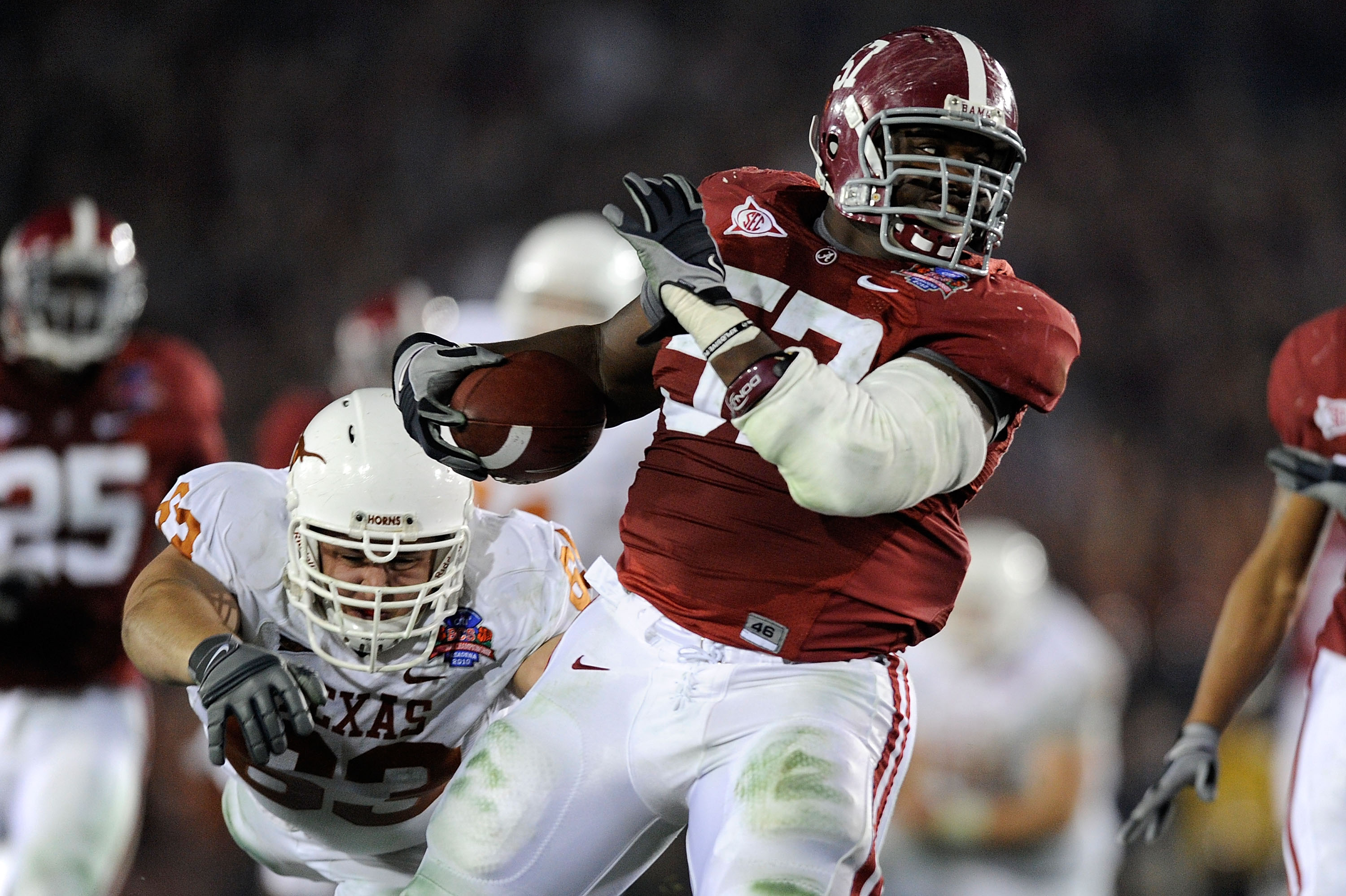 PASADENA, CA - JANUARY 07:  Lineman Marcell Dareus #57 of the Alabama Crimson Tide runs with the ball after an interception as guard Michael Huey #63 of the Texas Longhorns attempts to tackle during the second quarter of the Citi BCS National Championship
