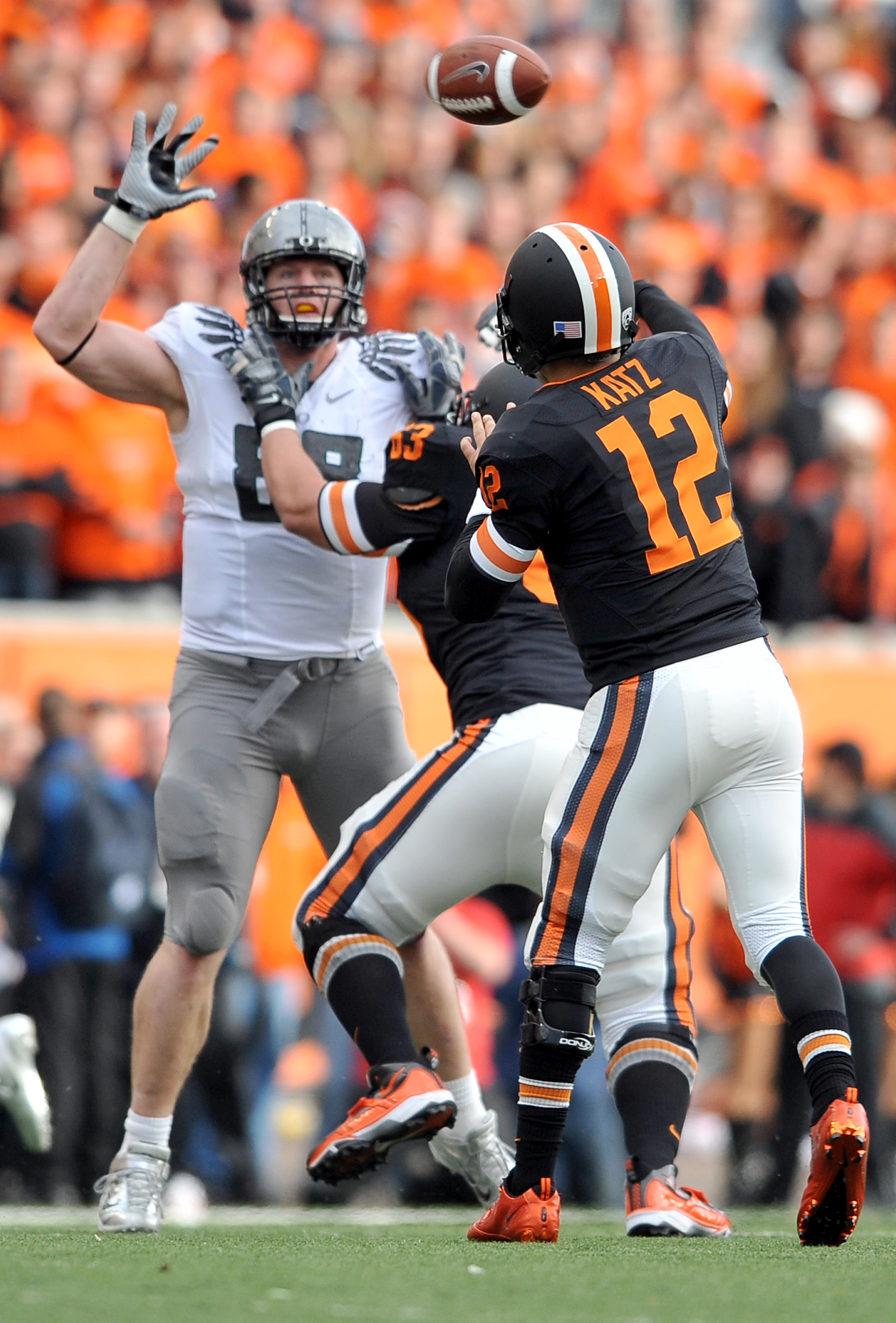 CORVALLIS, OR - DECEMBER 4: Quarterback Ryan Katz #12 of the Oregon State Beavers tries to pass the ball over the outstretched arm of Brandon Bair #88 of the Oregon Ducks in the second quarter the game at Reser Stadium on December 4, 2010 in Corvallis, Or
