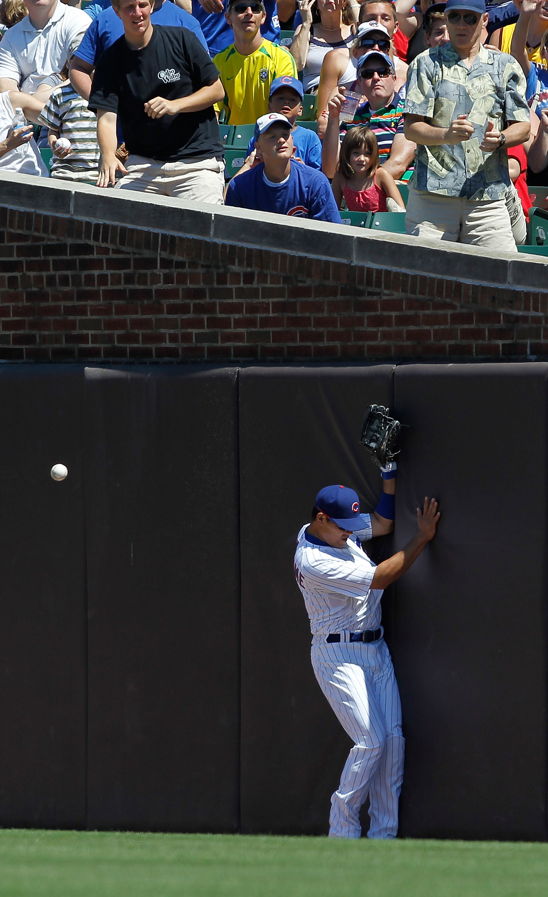 CHICAGO - JUNE 30: Kosuke Fukudome #1 of the Chicago Cubs hits the padded outfield wall while a foul ball bounces over his head during a game against the Pittsburgh Pirates at Wrigley Field on June 30, 2010 in Chicago, Illinois. The Pirates defeated the C