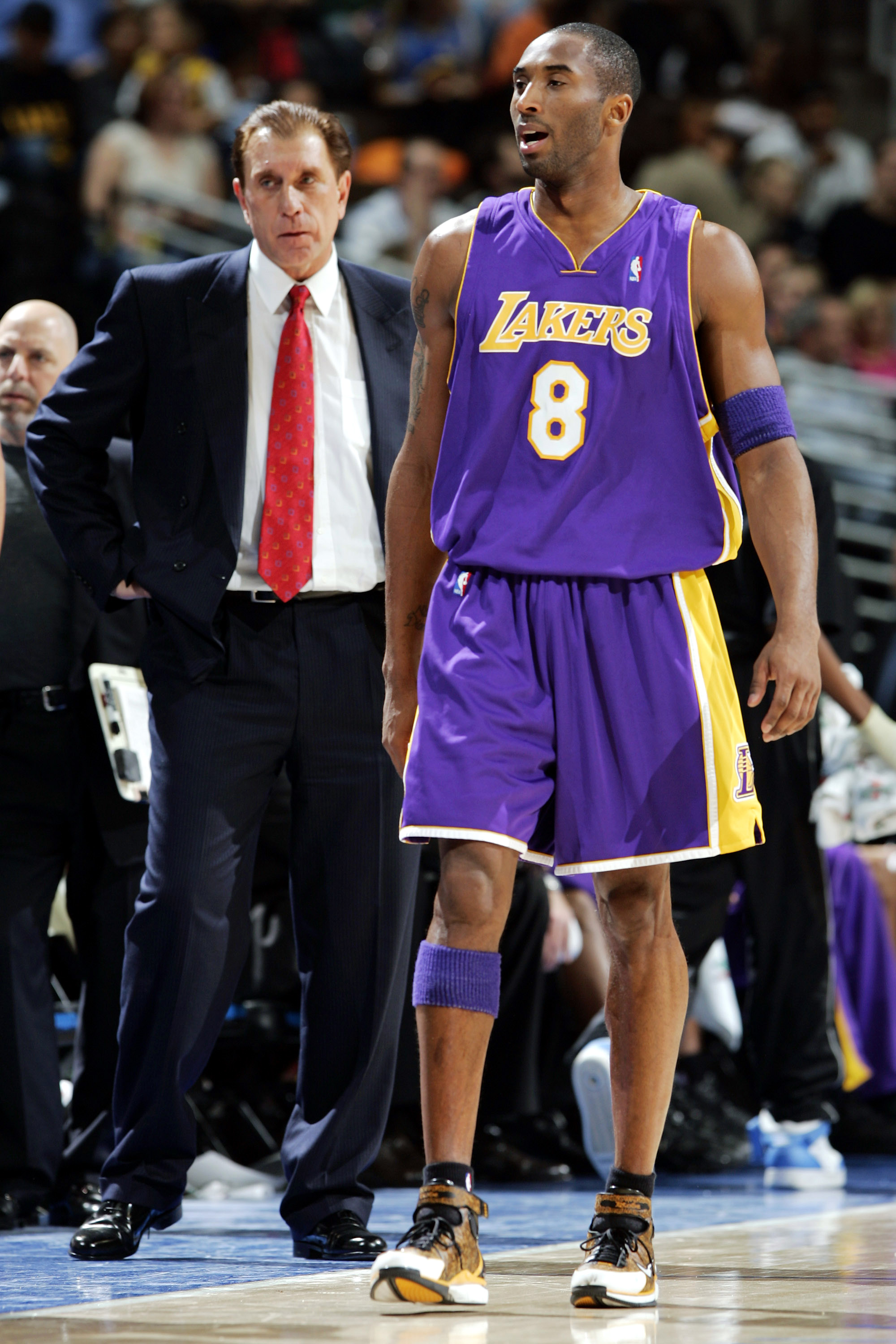 DENVER - JANUARY 12:  Kobe Bryant #8 of the Los Angeles Lakers walks back onto the court with head coach Rudy Tomjanovich behind him during the first half against the Denver Nuggets on January 12, 2005 at the Pepsi Center in Denver, Colorado. NOTE TO USER