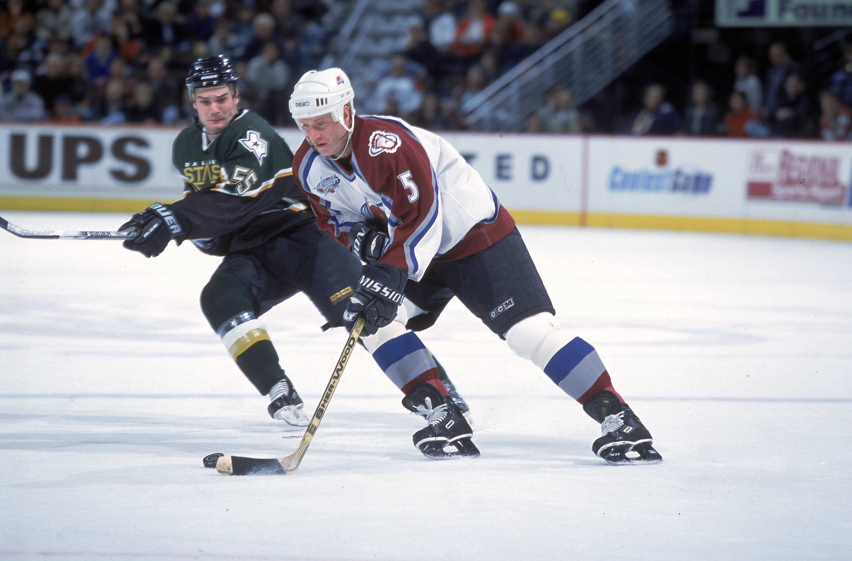 1 Dec 2000:  Alexei Gusarov #5 of the Colorado Avalanche controls the puck as Tyler Bouck #55 of the Dallas Stars moves in at the Pepsi Center in Denver, Colorado. The Avelanche defeated the Stars 4-2.Mandatory Credit: Brian Bahr  /Allsport