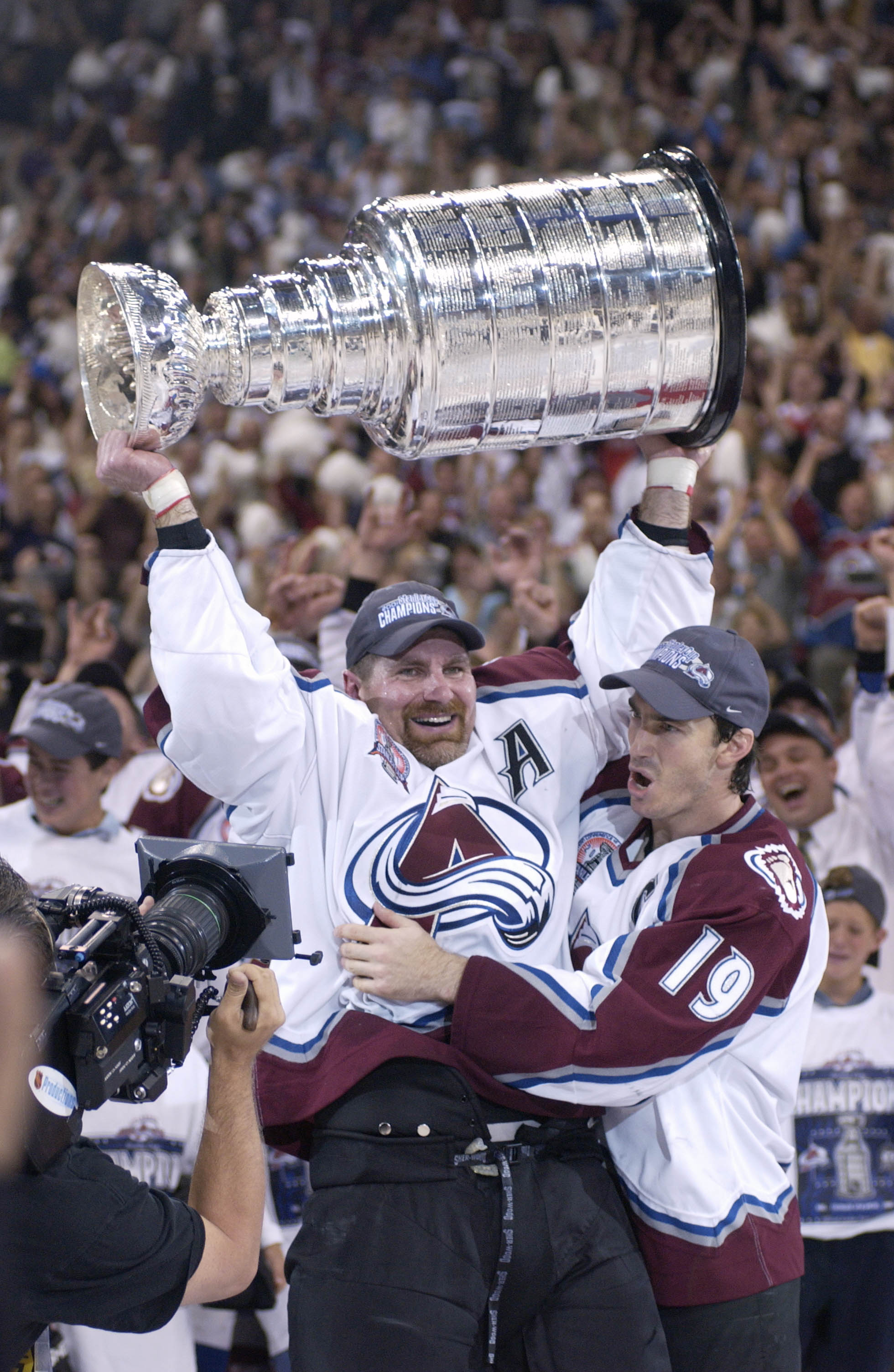 9 Jun 2001:  Ray Bourque #77 of the Colorado Avalanche lifts the cup as teammate Joe Sakic #19 hugs after the Colorado Avalanche defeated the New Jersey Devils 3-1 in game seven of the NHL Stanley Cup Finals at Pepsi Center in Denver, Colorado.  The Avala