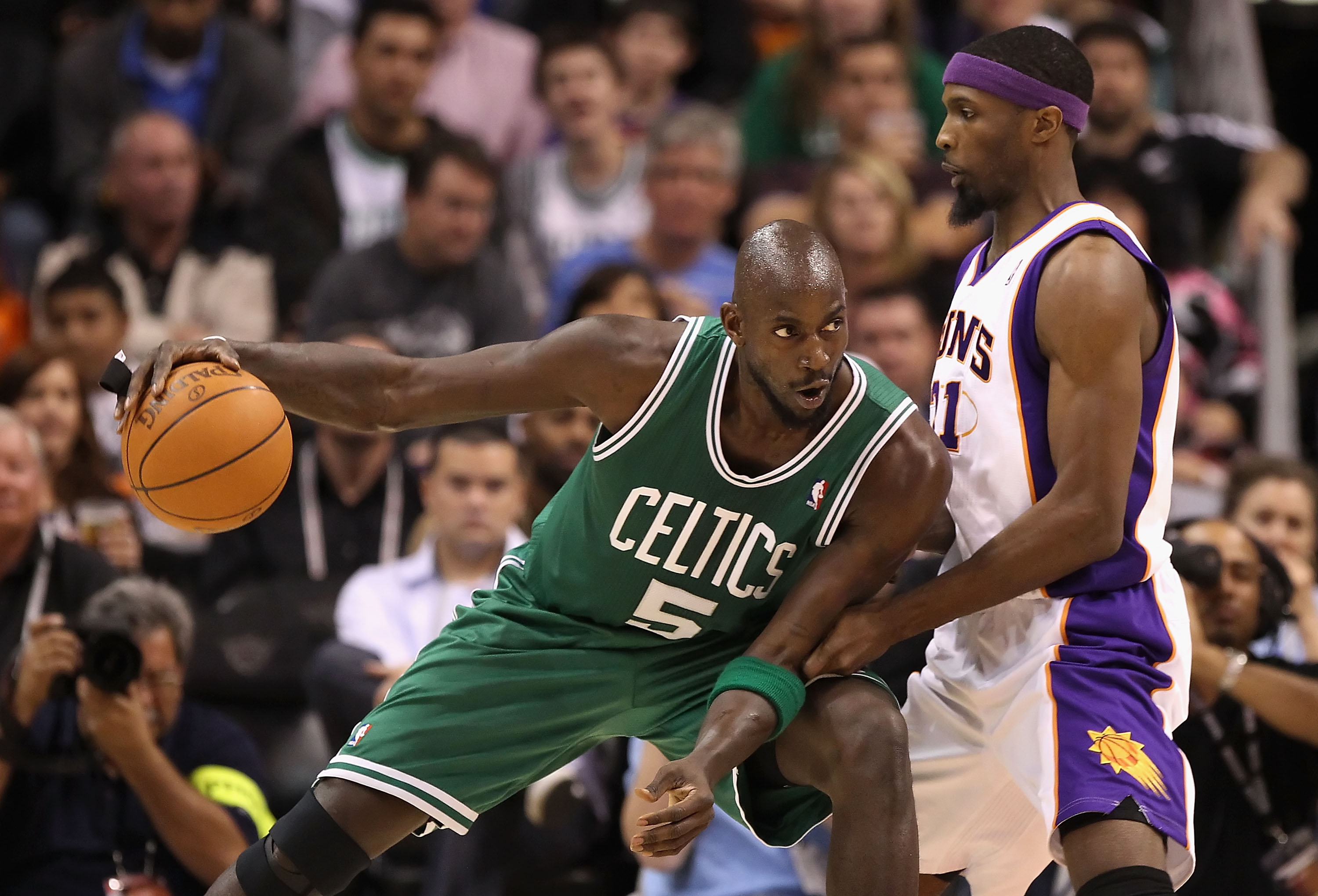 PHOENIX, AZ - JANUARY 28:  Kevin Garnett #5 of the Boston Celtics handles the ball guarded by Hakim Warrick #21 of the Phoenix Suns during the NBA game at US Airways Center on January 28, 2011 in Phoenix, Arizona.  The Suns defeated the Celtics 88-71.  NO