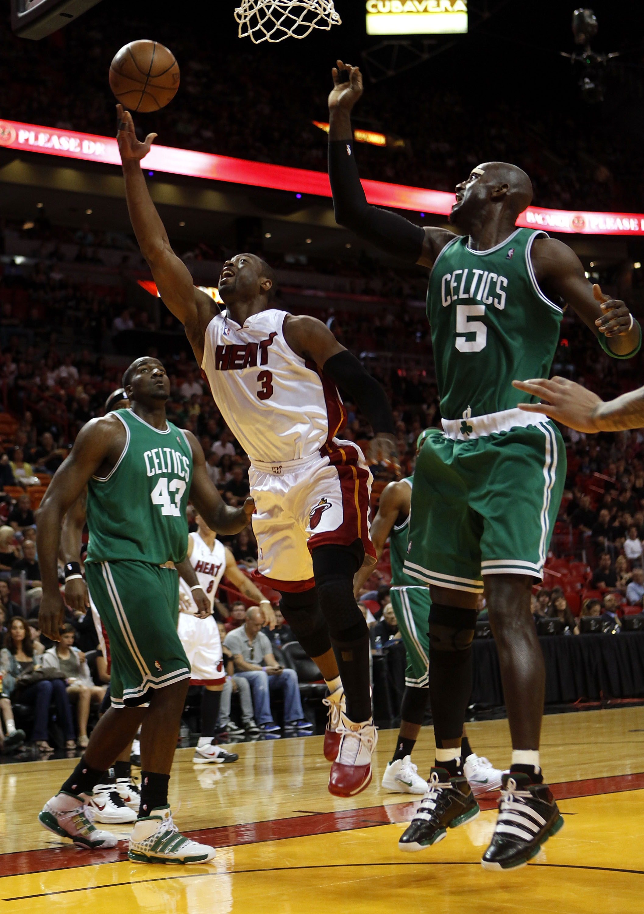 MIAMI - APRIL 25:  Guard Dwyane Wade #3 of the Miami Heat scores against Center Kendrick Perkins #43 and Forward Kevin Garnett #5 of the Boston Celtics in Game Four of the Eastern Conference Quarterfinals during the 2010 NBA Playoffs at American Airlines