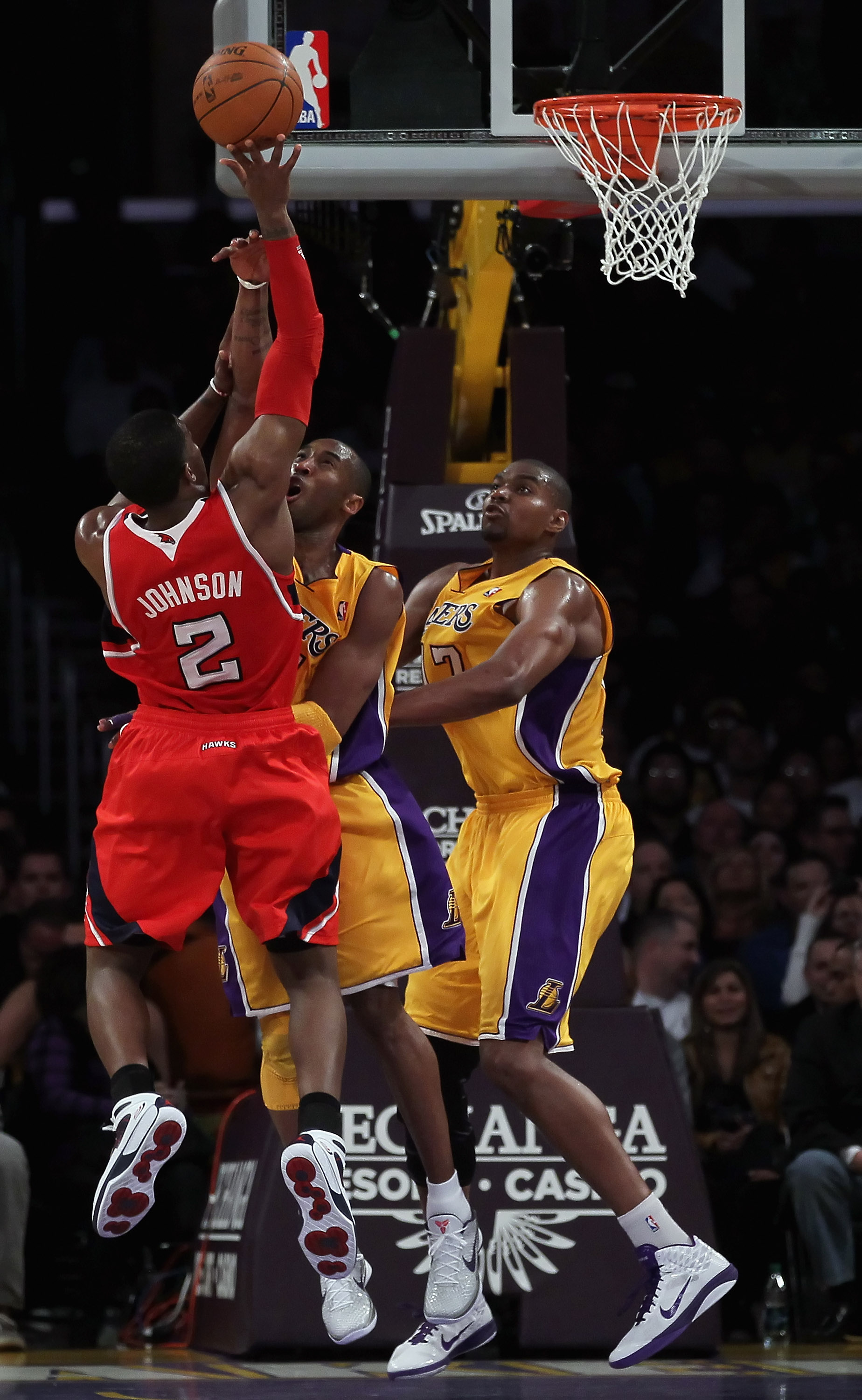 LOS ANGELES, CA - FEBRUARY 22:  (L-R) Joe Johnson #2 of the Atlanta Hawks shoots while being defended by Kobe Bryant #24 and Andrew Bynum #17 of the Los Angeles Lakers in the first half at Staples Center on February 22, 2011 in Los Angeles, California. Th