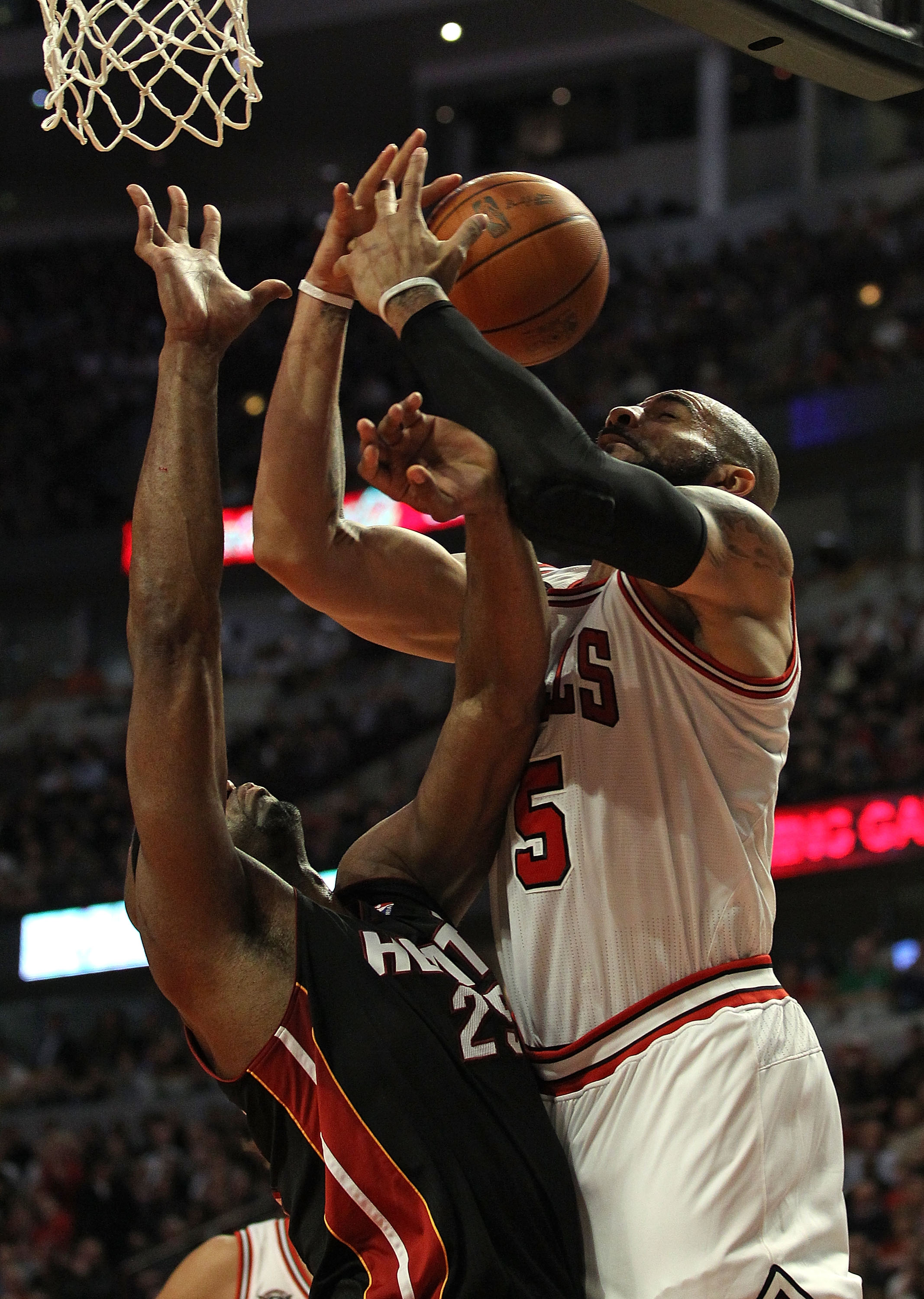 CHICAGO, IL - FEBRUARY 24: Carlos Boozer #5 of the Chicago Bulls is fouled while shooting by Eric Dampier #25 of the Miami Heat at the United Center on February 24, 2011 in Chicago, Illinois. The Bulls defeated the Heat 93-89. NOTE TO USER: User expressly