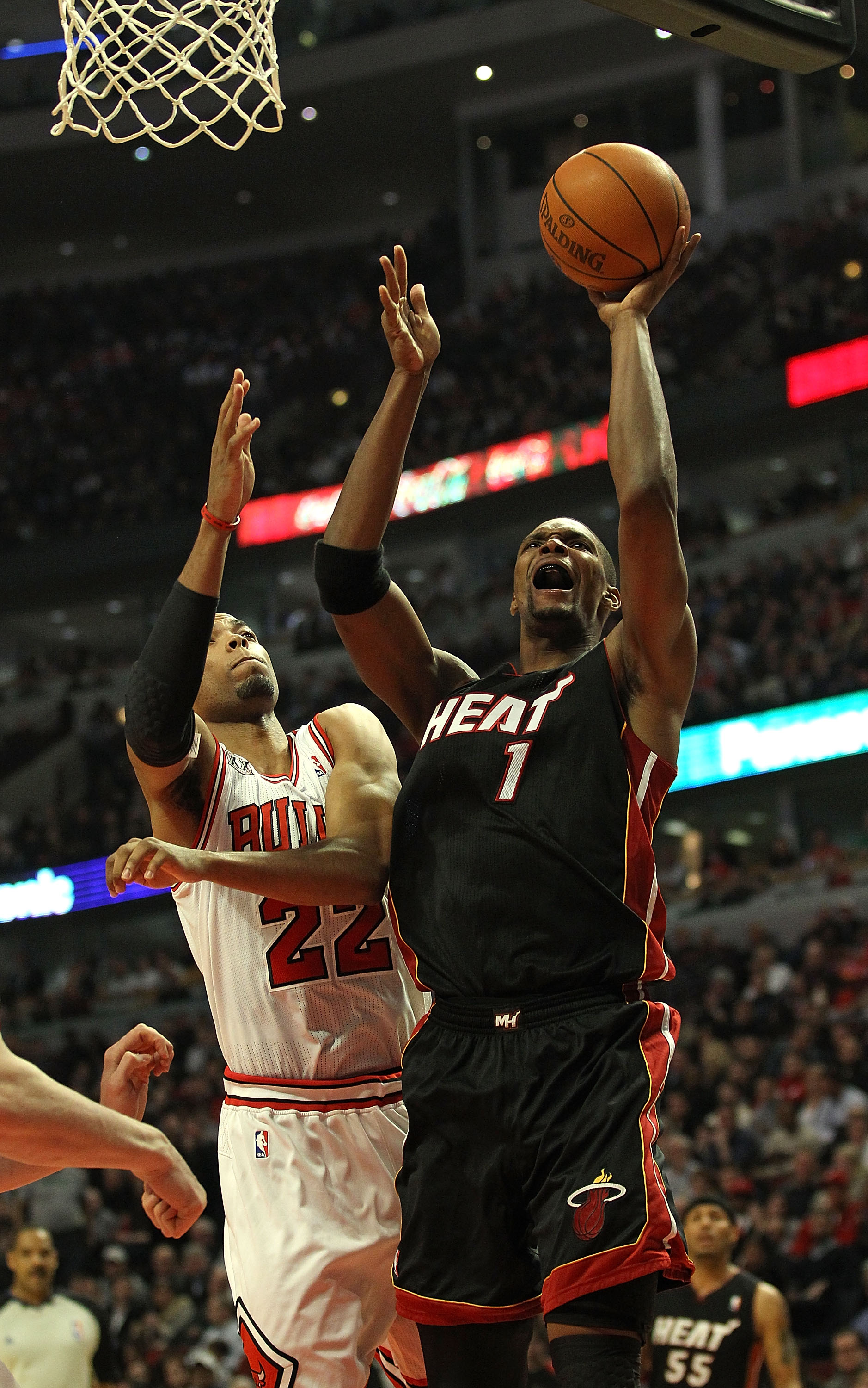 CHICAGO, IL - FEBRUARY 24: Chris Bosh #1 of the Miami Heat puts up a shot under pressure from Taj Gibson #22 of the Chicago Bulls at the United Center on February 24, 2011 in Chicago, Illinois. NOTE TO USER: User expressly acknowledges and agrees that, by