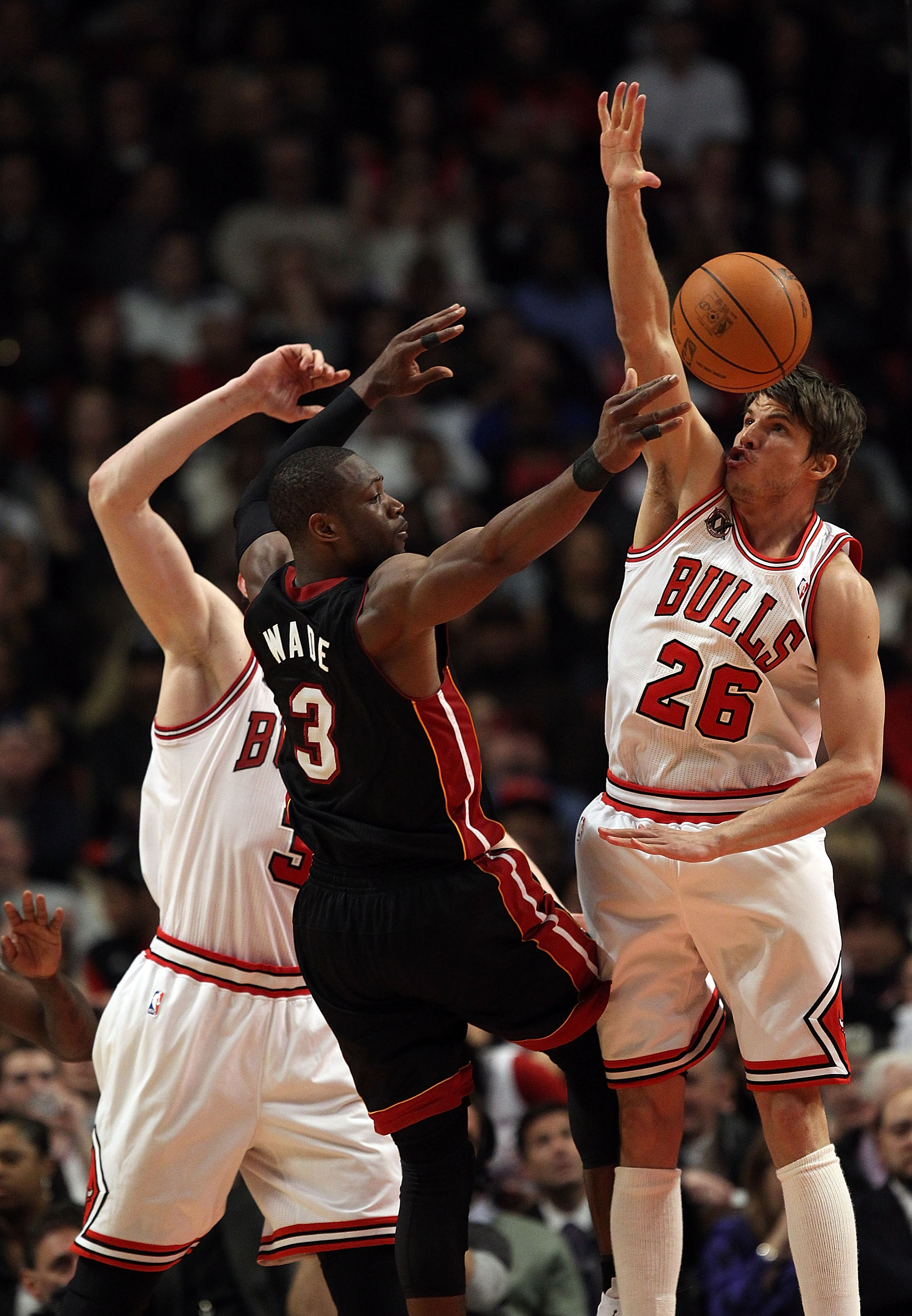 CHICAGO, IL - FEBRUARY 24: Dwyane Wade #3 of the Miami Heat passes the ball under pressure from Omer Asik #3 and Kyle Korver #26 of the Chicago Bulls at the United Center on February 24, 2011 in Chicago, Illinois. The Bulls defeated the Heat 93-89. NOTE T