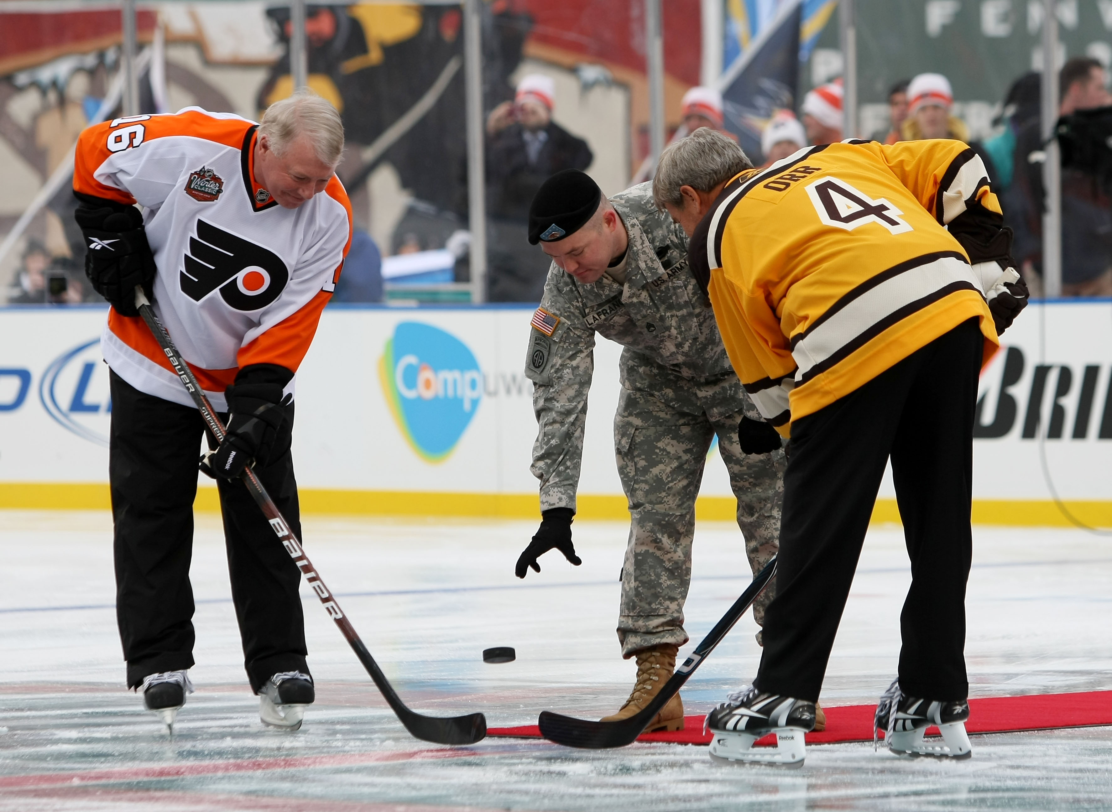 BOSTON - JANUARY 01:  Staff Sergeant Ryan R. LaFrance (C) drops the ceremonial first puck for Bobby Clarke #16 (L) honorary captain of the Philadelphia Flyers and Bobby Orr #4 (R) honorary captain of the Boston Bruins during the 2010 Bridgestone Winter Cl