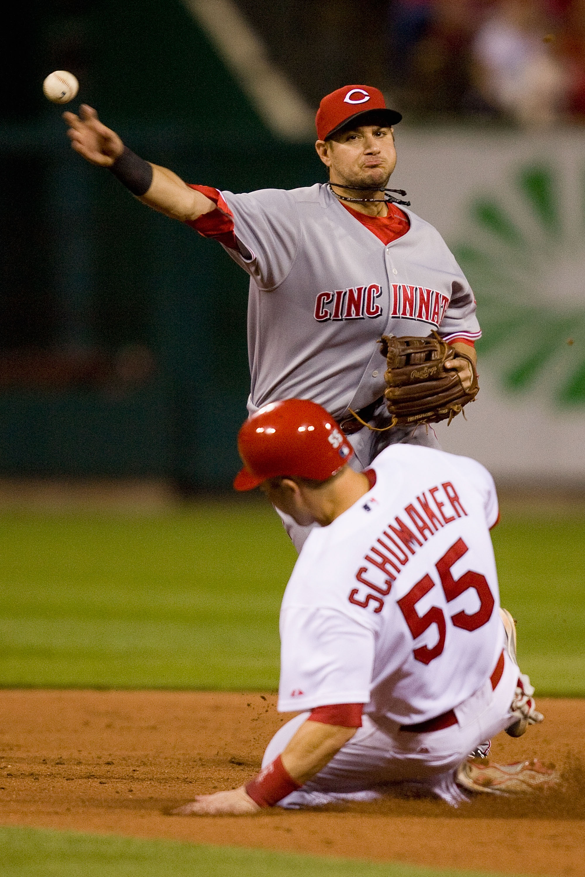 ST. LOUIS - SEPTEMBER 3: Paul Janish #7 of the Cincinnati Reds turns a double play over Skip Schumaker #55 of the St. Louis Cardinals at Busch Stadium on September 3, 2010 in St. Louis, Missouri.  The Cardinals beat the Reds 3-2.  (Photo by Dilip Vishwana
