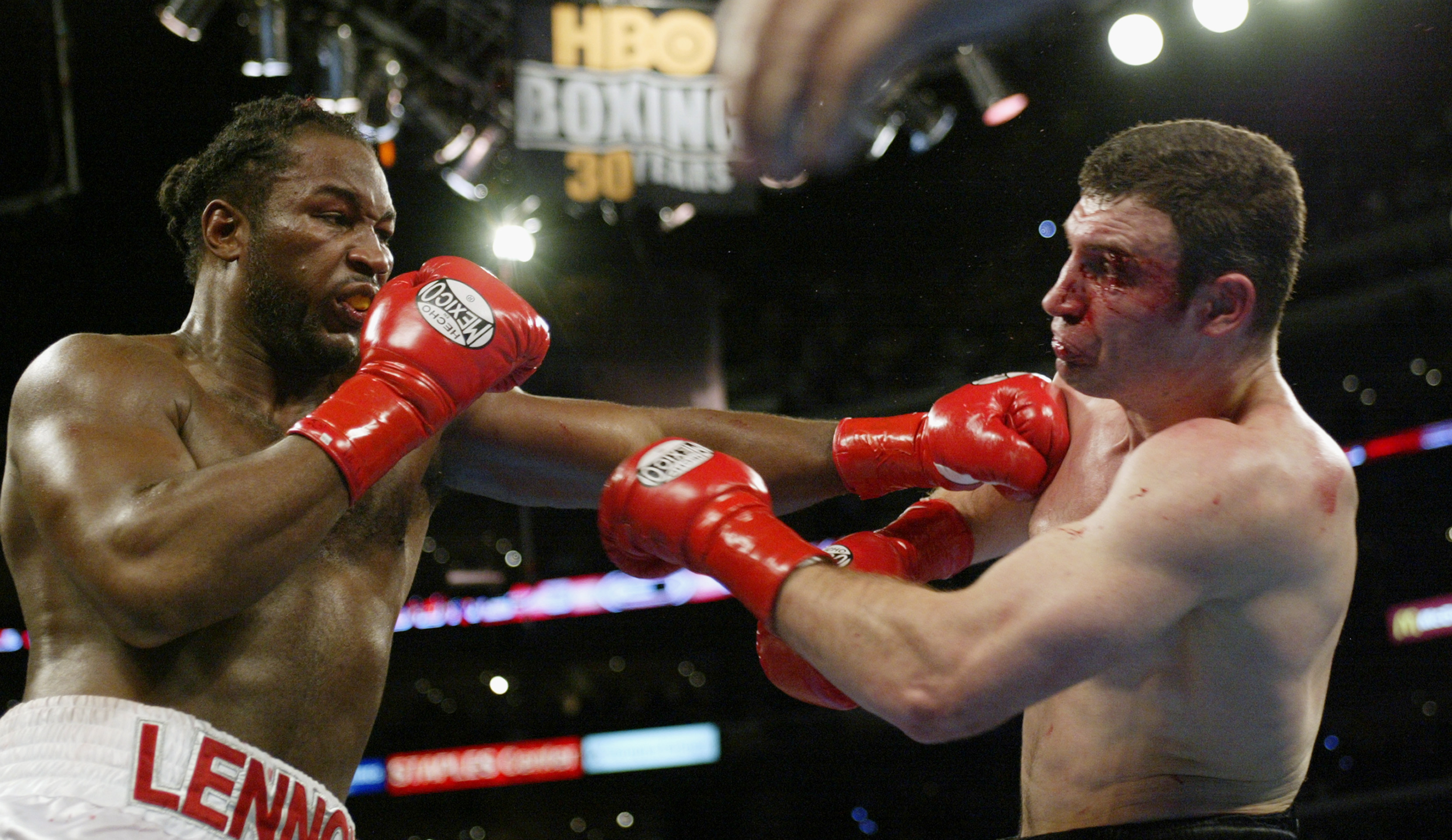 LOS ANGELES - JUNE 21:  Lennox Lewis (left) hits Vitali Klitschko (right) during their WBC and IBO World Heavyweight Championship bout at the Staples Center on June 21, 2003 in Los Angeles, California.  Lennox Lewis (41-2-1) was handed a sixth-round techn