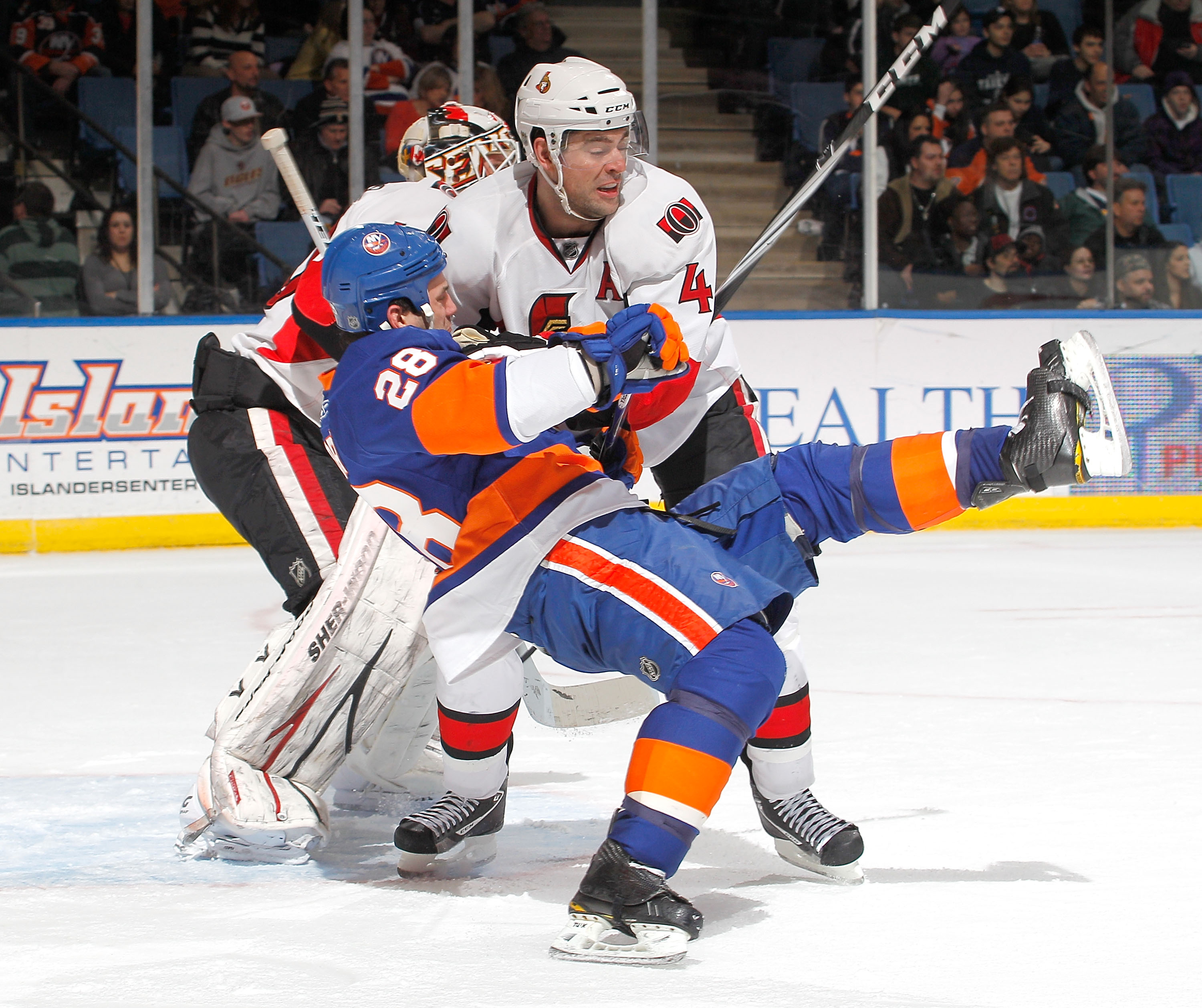 UNIONDALE, NY - FEBRUARY 05:  Chris Phillips #4 of the Ottawa Senators gets a penalty here as he takes down Zenon Konopka #28 of the New York Islanders during the second period of an NHL hockey game at the Nassau Coliseum on February 5, 2011 in Uniondale,