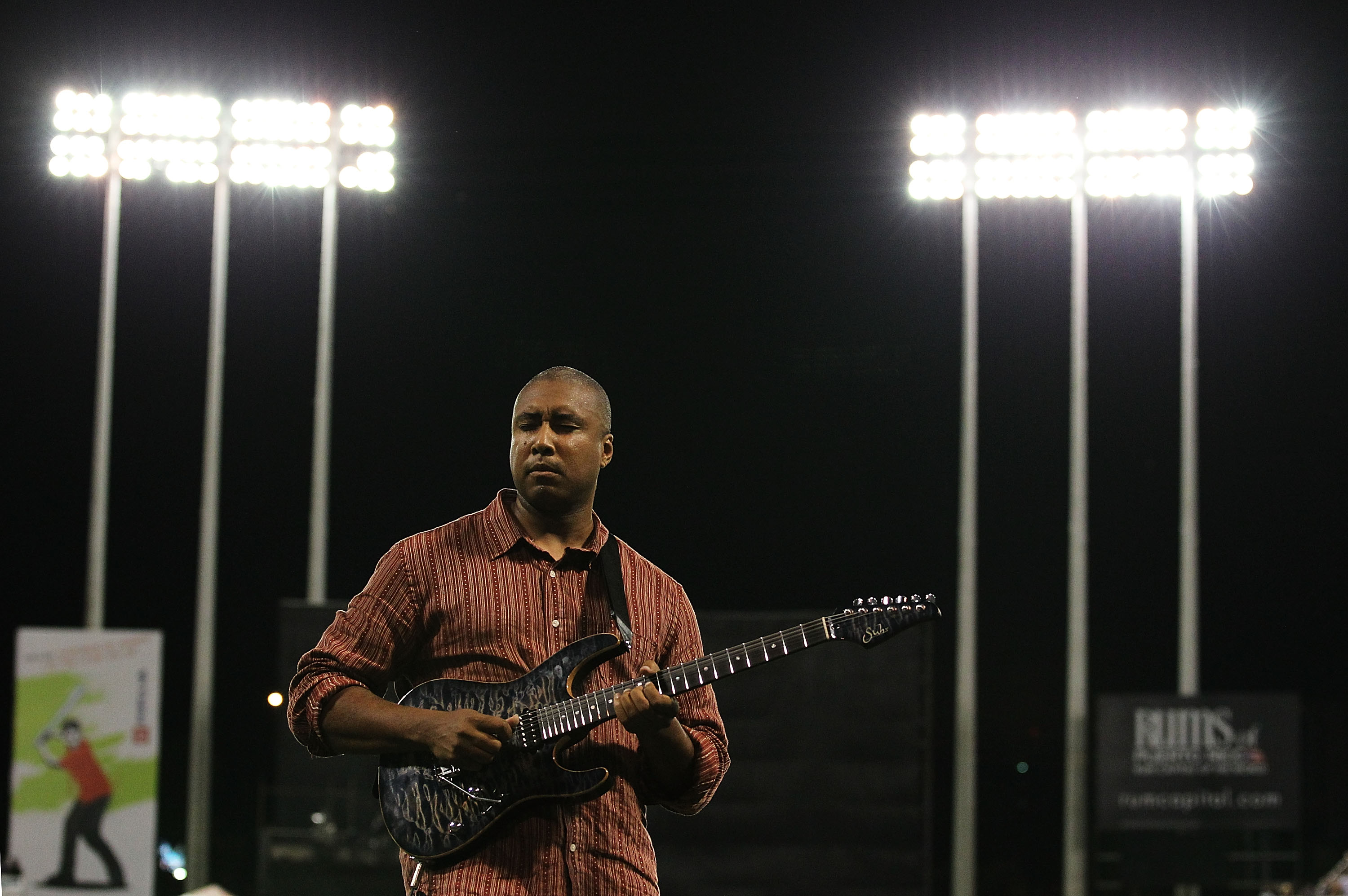 SAN JUAN, PUERTO RICO - JUNE 30:  Musician and former baseball player of the New York Yankees Bernie Williams plays the national anthem on his guitar before the game between the New York Mets and the Florida Marlins at Hiram Bithorn Stadium on June 30, 20