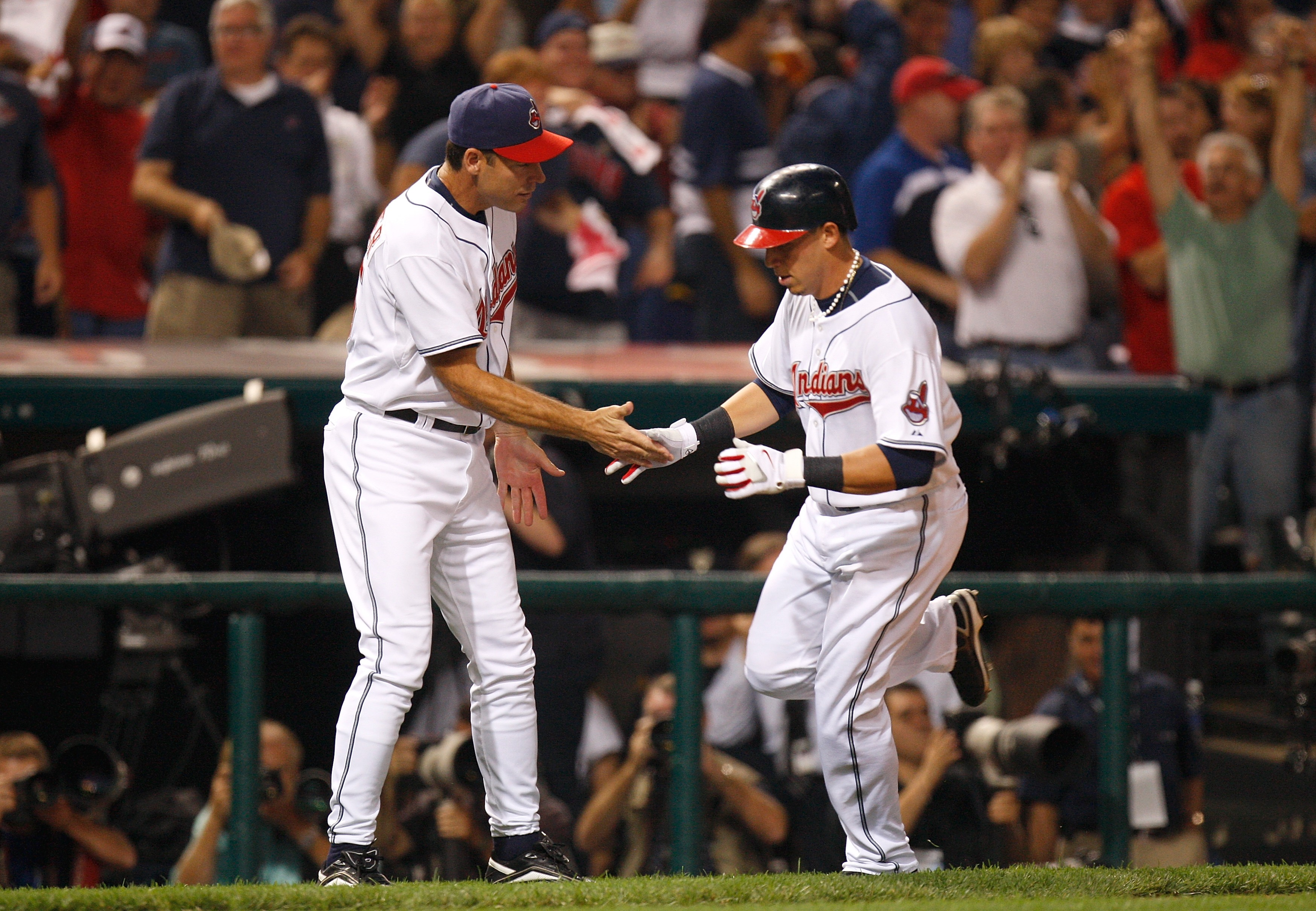 CLEVELAND - OCTOBER 04:  Asdrubal Cabera #13 of the Cleveland Indians is congratulated thirdbase coach Joel Skinner (R) as he heads to home plate after hitting a solo home run in the bottom of the third inning against the New York Yankees during Game One