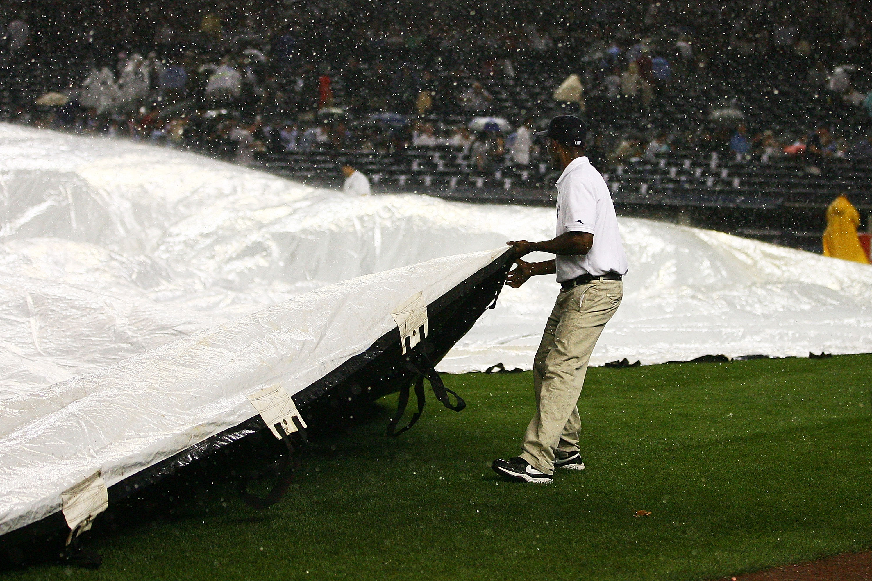 NEW YORK - SEPTEMBER 22:  Members of the New York Yankees grounds keeping crew cover the field at the start of a rain delay during the third inning against the Tampa Bay Rays on September 22, 2010 at Yankee Stadium in the Bronx borough of New York City.