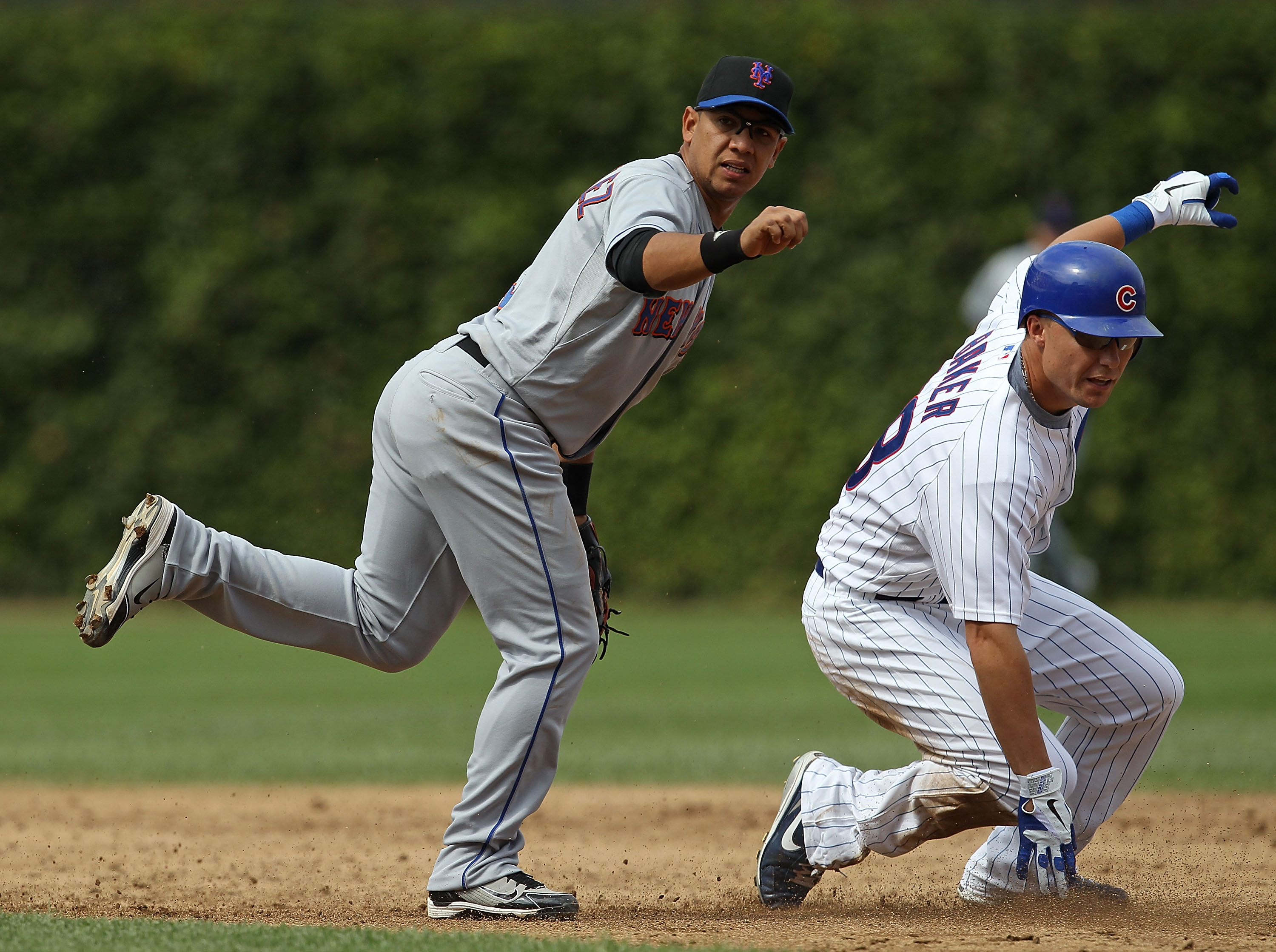 CHICAGO - SEPTEMBER 05: Luis Hernandez #3 of the New York Mets hops out of the way of Jeff Baker #28 of the Chicago Cubs after turning a double play at Wrigley Field on September 5, 2010 in Chicago, Illinois. The Mets defeated the Cubs 18-5. (Photo by Jon