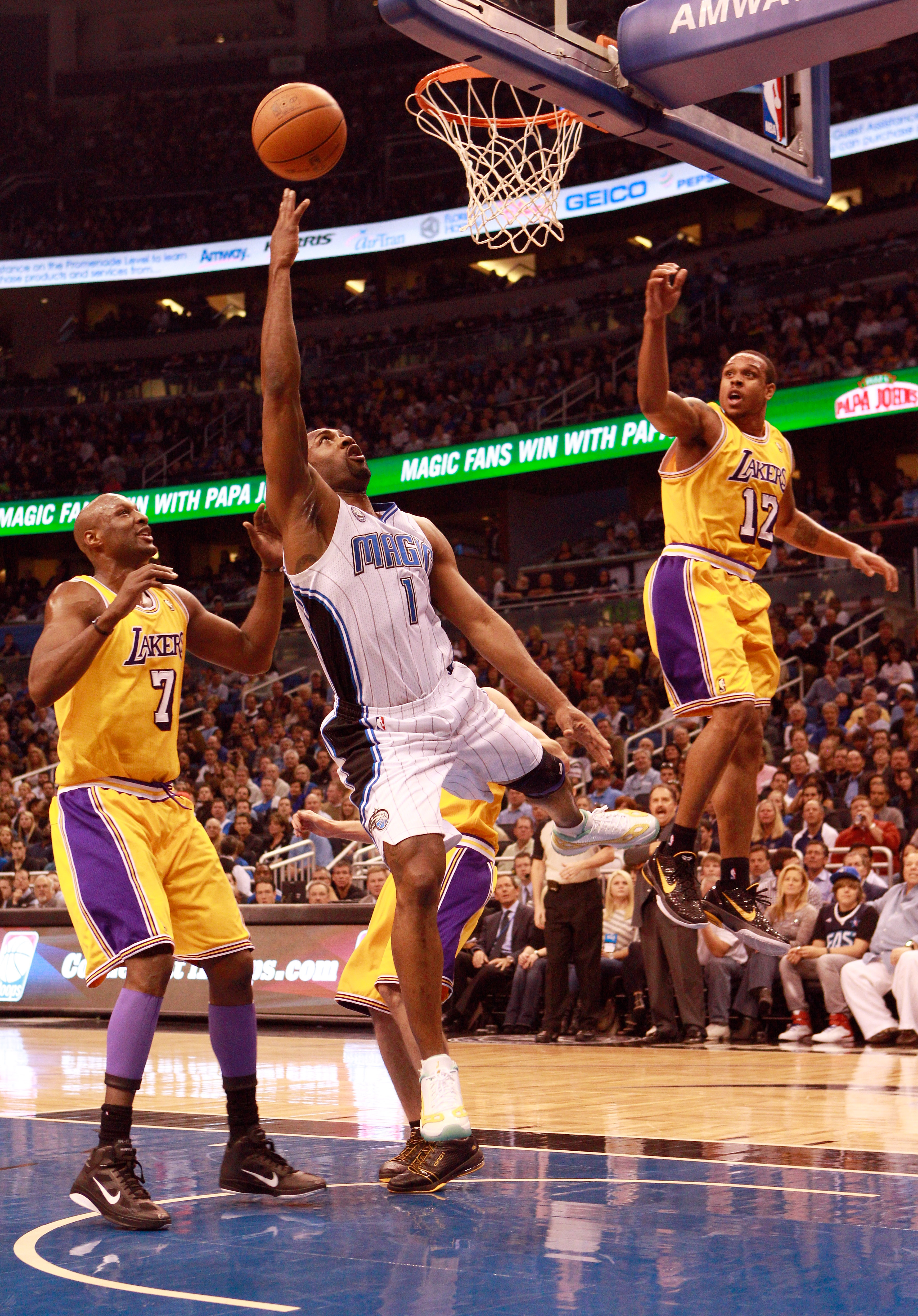 ORLANDO, FL - FEBRUARY 13:  Gilbert Arenas #1 of the Orlando Magic attempts a shot against Lamar Odom #7 and Shannon Brown #12 of the Los Angeles Lakers during the game at Amway Arena on February 13, 2011 in Orlando, Florida.  NOTE TO USER: User expressly