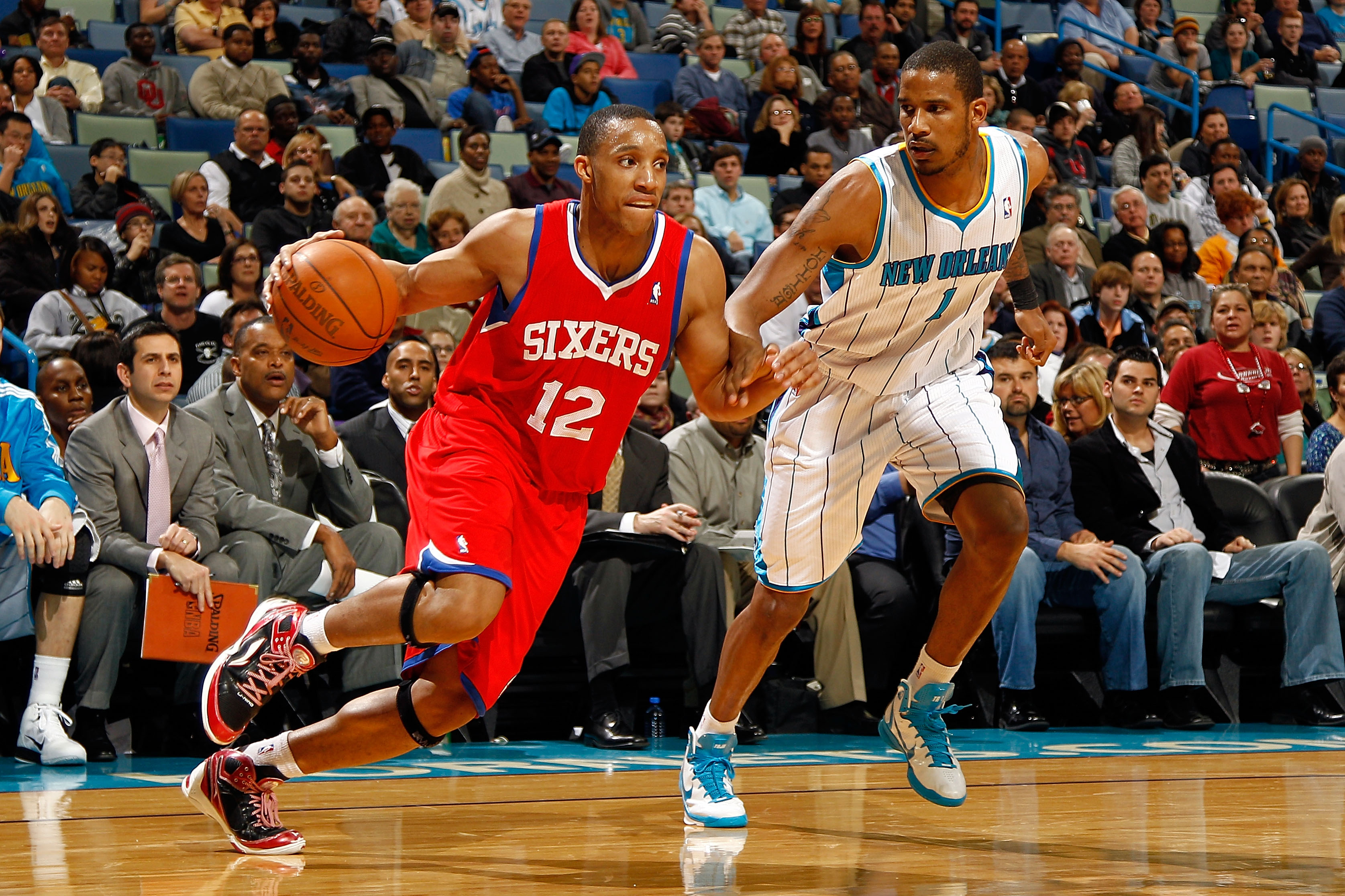 NEW ORLEANS, LA - JANUARY 03:  Evan Turner #12 of the Philadelphia 76ers drives on Trevor Ariza #1 of the New Orleans Hornets in the second half at New Orleans Arena on January 3, 2011 in New Orleans, Louisiana. NOTE TO USER: User expressly acknowledges a