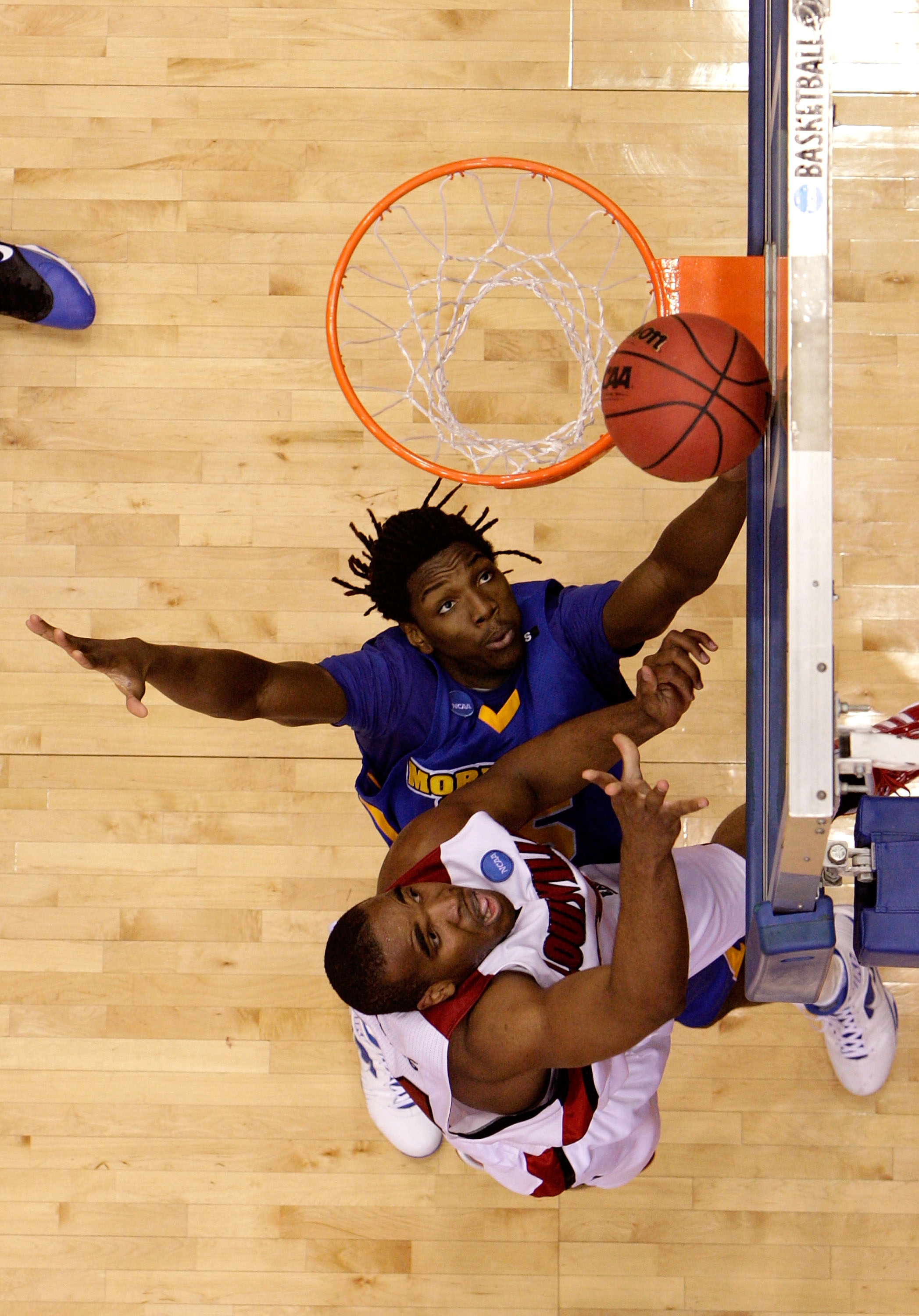 DAYTON, OH - MARCH 20: Samardo Samuels #24 of the Louisville Cardinals drives to the hoop against Kenneth Faried #35 of the Morehead State Eagles during the first round of the NCAA Division I Men's Basketball Tournament at the University of Dayton Arena o