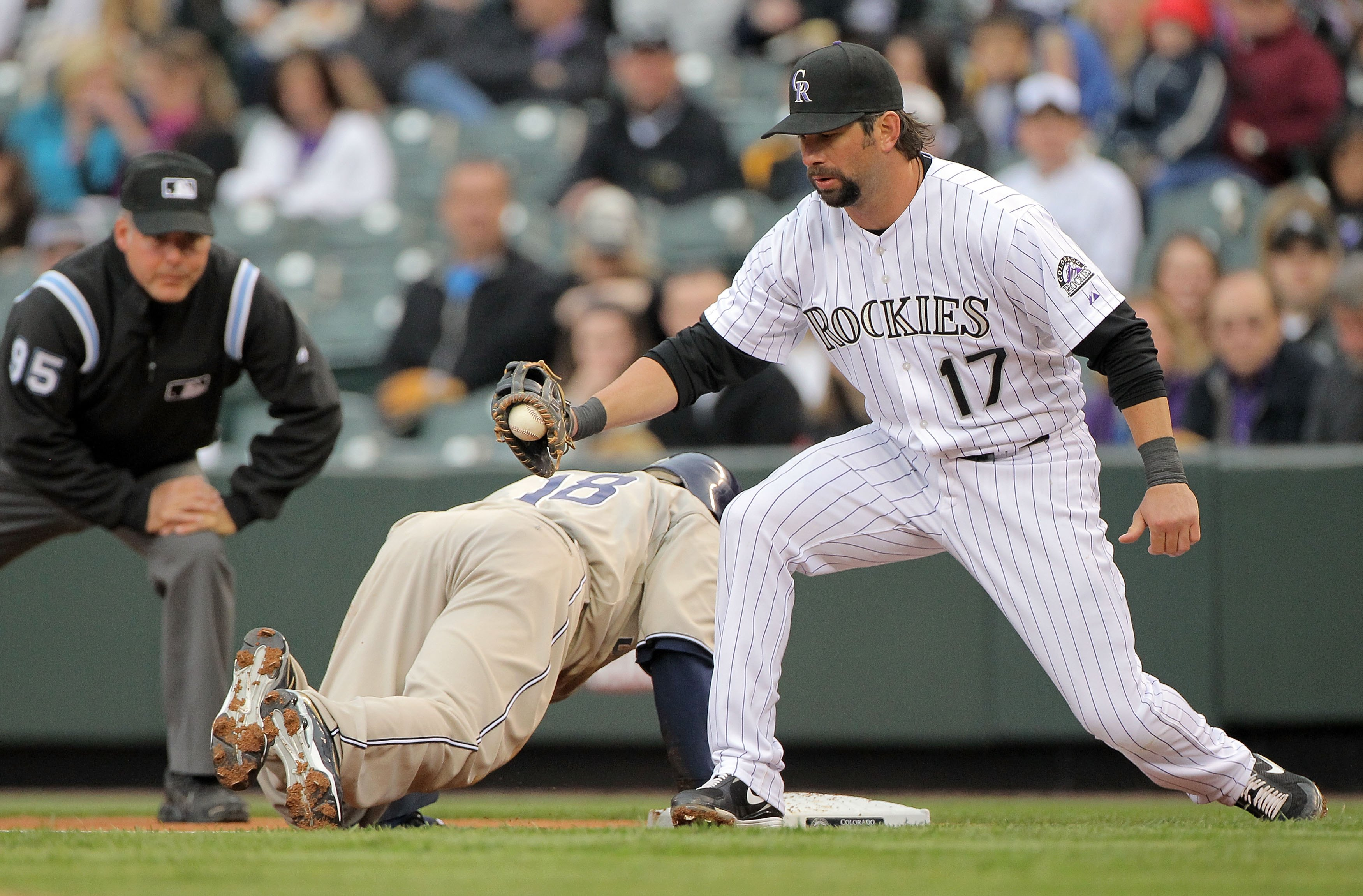 DENVER - APRIL 10:  First baseman Todd Helton #17 of the Colorado Rockies takes a pick off throw at first base to hold Tony Gwynn Jr. #18 of the San Diego Padres as umpire Tim Timmons oversees the play during MLB action at Coors Field on April 10, 2010 in