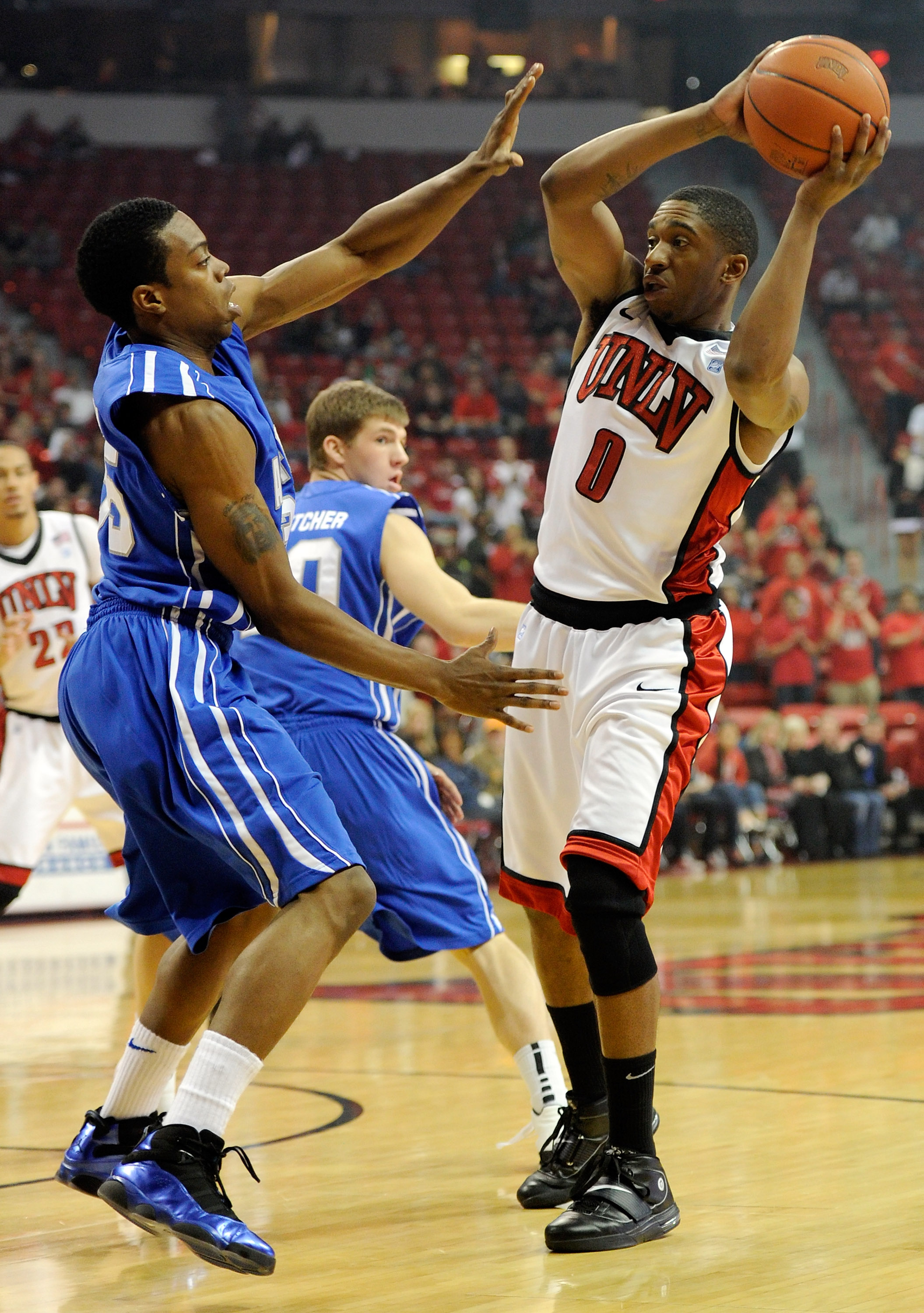 LAS VEGAS, NV - FEBRUARY 15:  Oscar Bellfield #0 of the UNLV Rebels looks to pass against Evan Washington #35 of the Air Force Falcons during their game at the Thomas & Mack Center February 15, 2011 in Las Vegas, Nevada. UNLV won 49-42.  (Photo by Ethan M