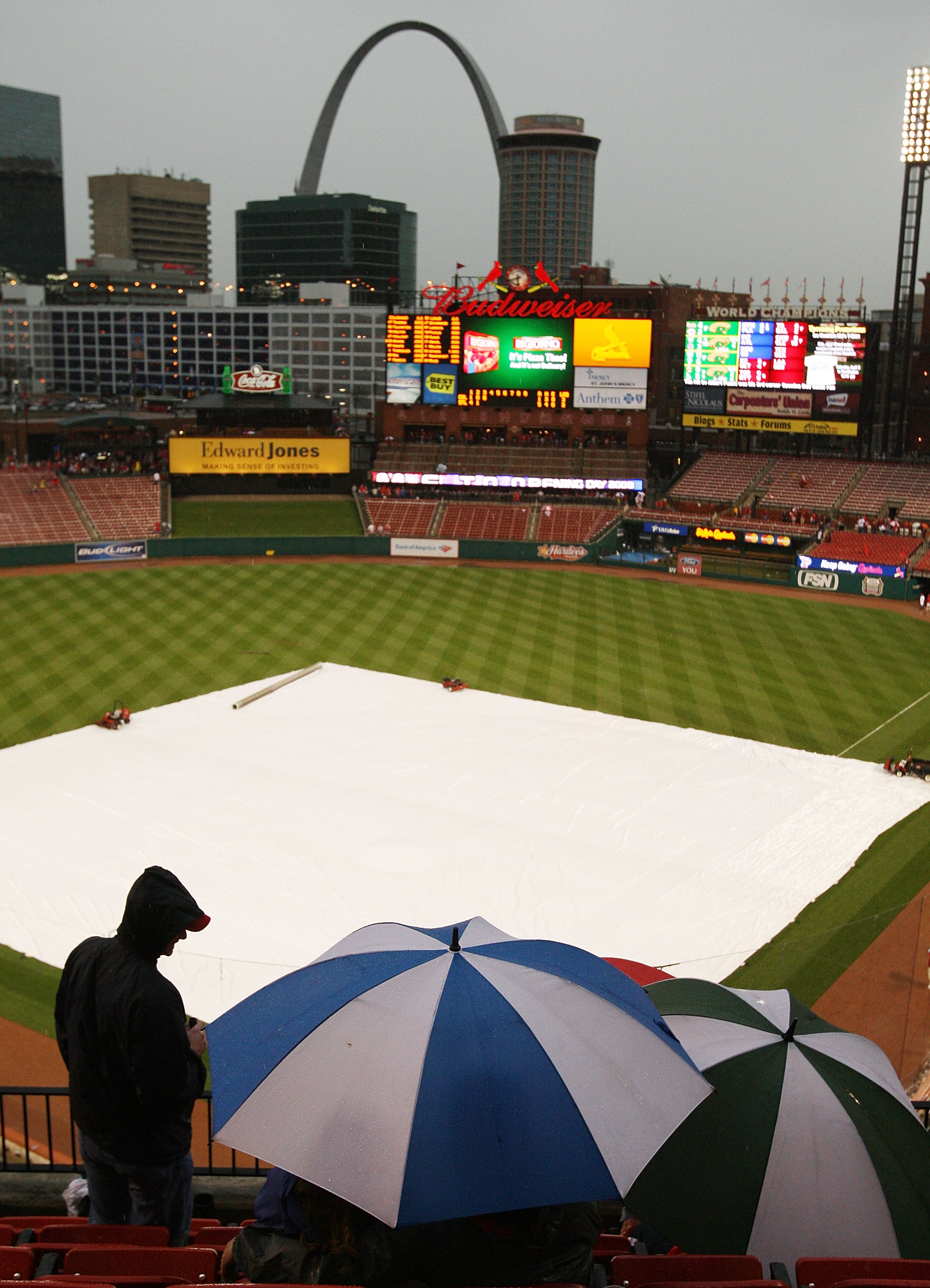 ST. LOUIS - MARCH 31:  Fans wait to see whether the St. Louis Cardinals home opener will continue after rain halted play in the third inning against the Colorado Rockies March 31,2008 at Busch Stadium in St. Louis, Missouri.  (Photo by Elsa/Getty Images)
