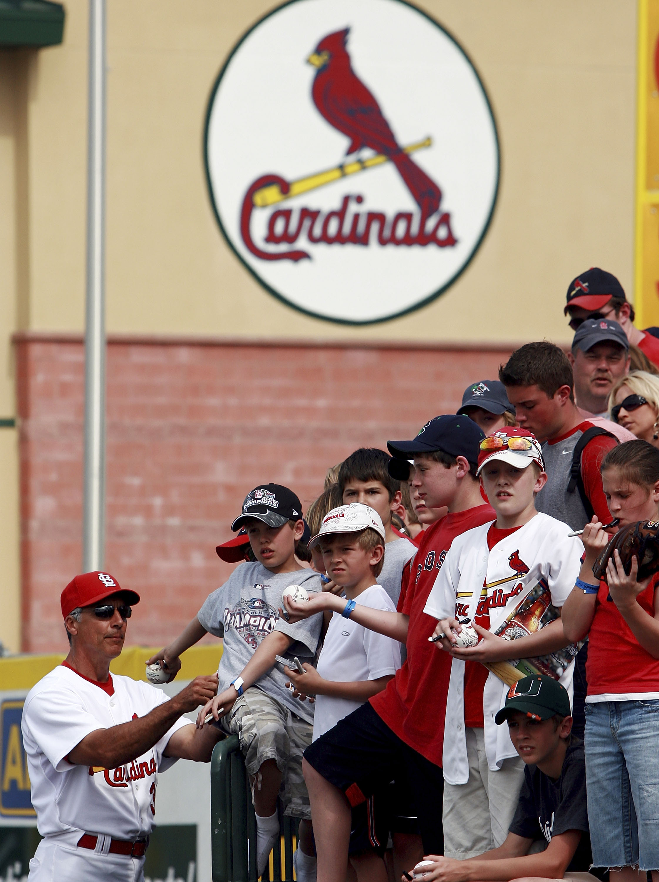 JUPITER, FL - MARCH 14:  Coach Dave McKay #39 of the St. Louis Cardinals signs autographs as fans look for the next player to leave the field after playing the Washington Nationals on March 14, 2007 at Roger Dean Stadium in Jupiter, Florida. The Nationals