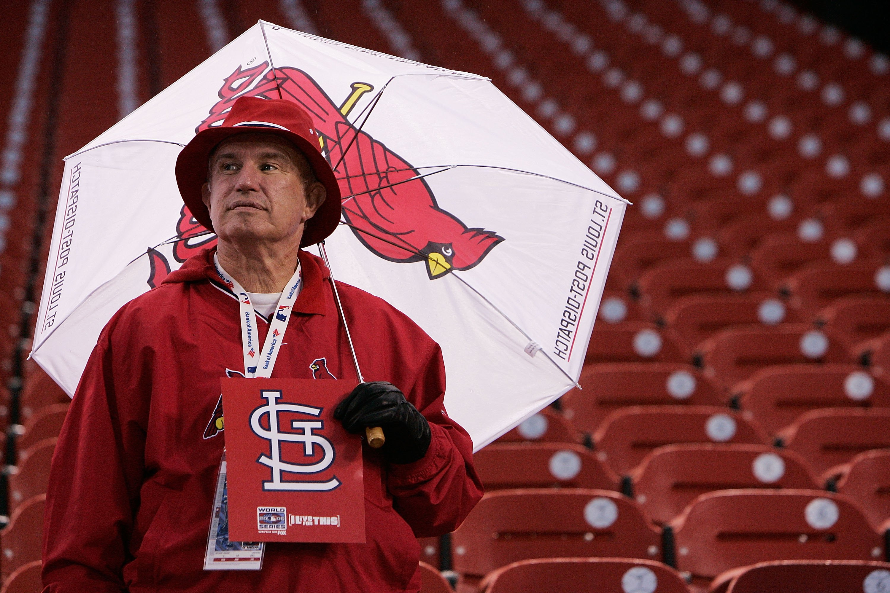 ST LOUIS - OCTOBER 25:  A Cardinals fan attempts to stay dry under an umbrella before the start of Game Four of the 2006 World Series between the Detroit Tigers and the St. Louis Cardinals on October 25, 2006 at Busch Stadium in St. Louis, Missouri.  (Pho