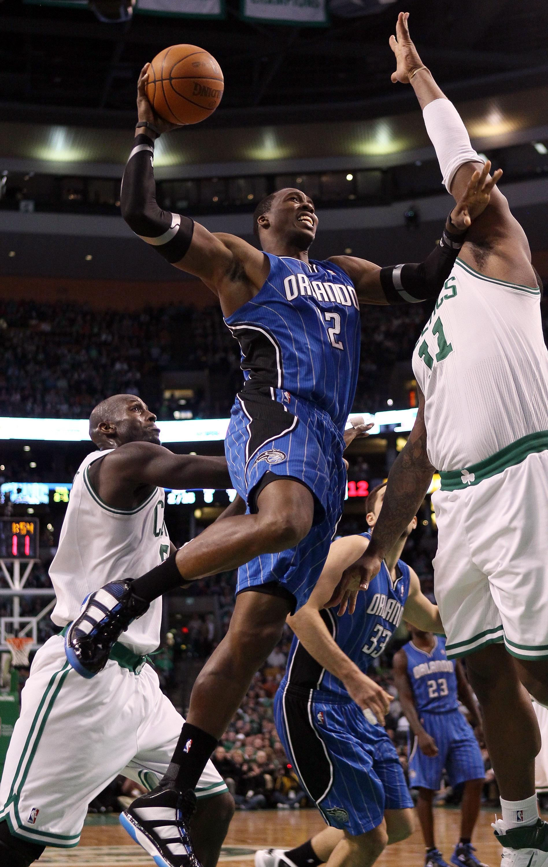 BOSTON, MA - FEBRUARY 06:  Dwight Howard #12 of the Orlando Magic heads for the basket as Kevin Garnett #5 and Glen Davis #11 of the Boston Celtics defend on February 6, 2011 at the TD Garden in Boston, Massachusetts. The Celtics defeated the Magic 91-80.