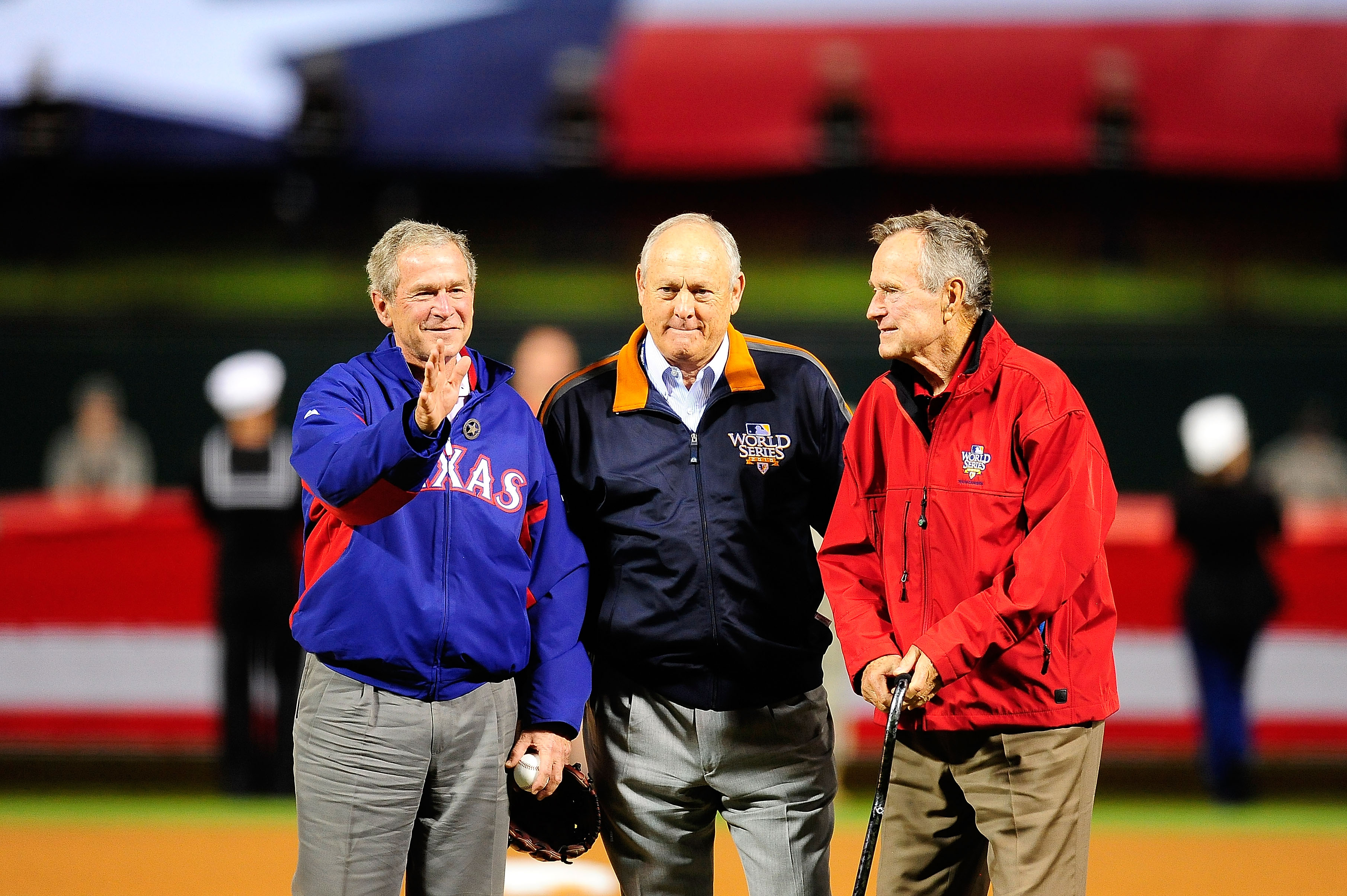 ARLINGTON, TX - OCTOBER 31:  Former President of the United States, George W. Bush (L), and his father Former President George H.W. Bush wave to the crowd with Rangers' President Nolan Ryan (C) before the Texas Rangers host the San Francisco Giants in Gam