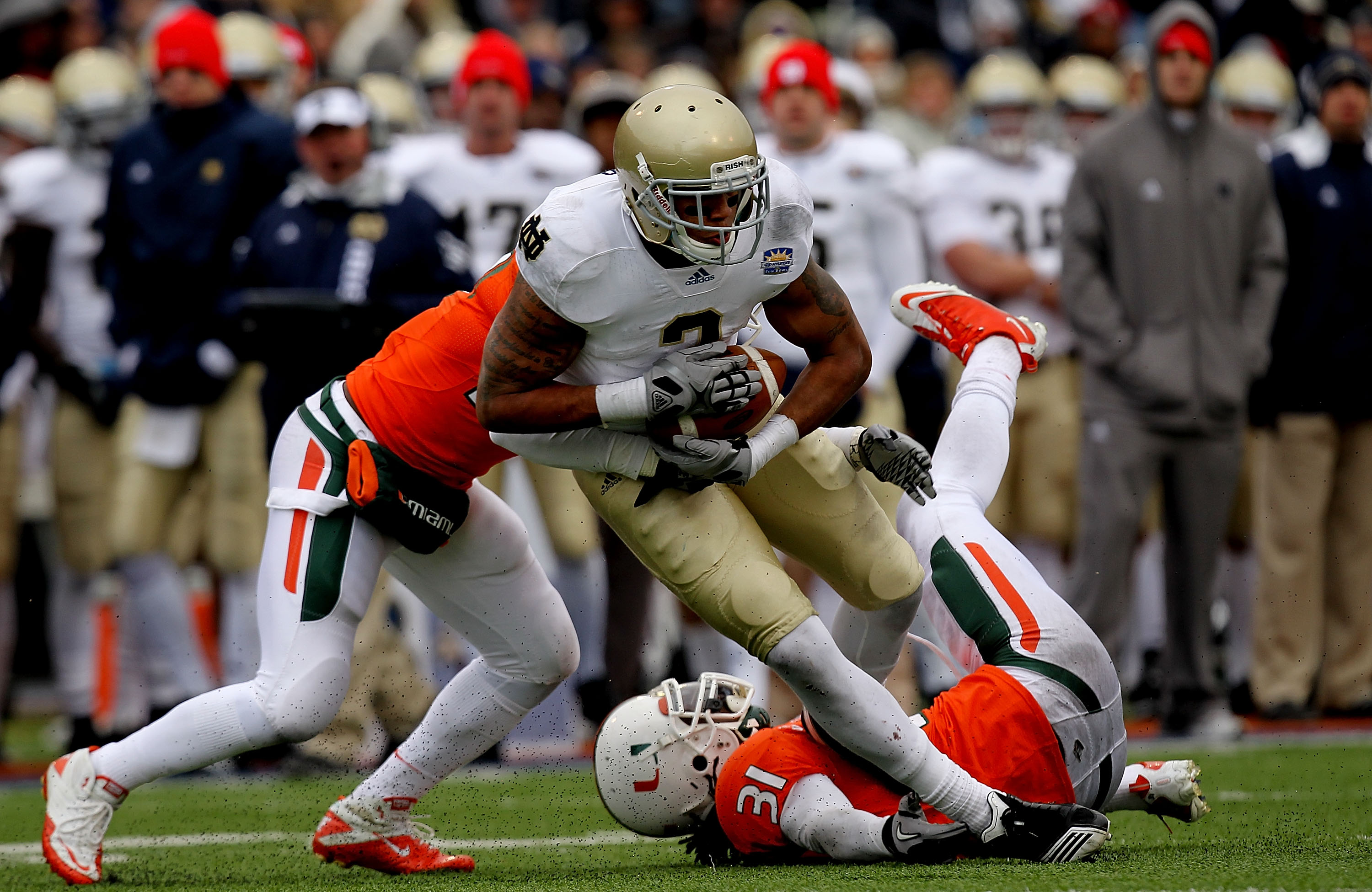 EL PASO, TX - DECEMBER 30:  Wide receiver Michael Floyd #3 of the Notre Dame Fighting Irish runs the ball past Jared Campbell #37 and Sean Spence #31 of the Miami Hurricanes at Sun Bowl on December 30, 2010 in El Paso, Texas.  (Photo by Ronald Martinez/Ge