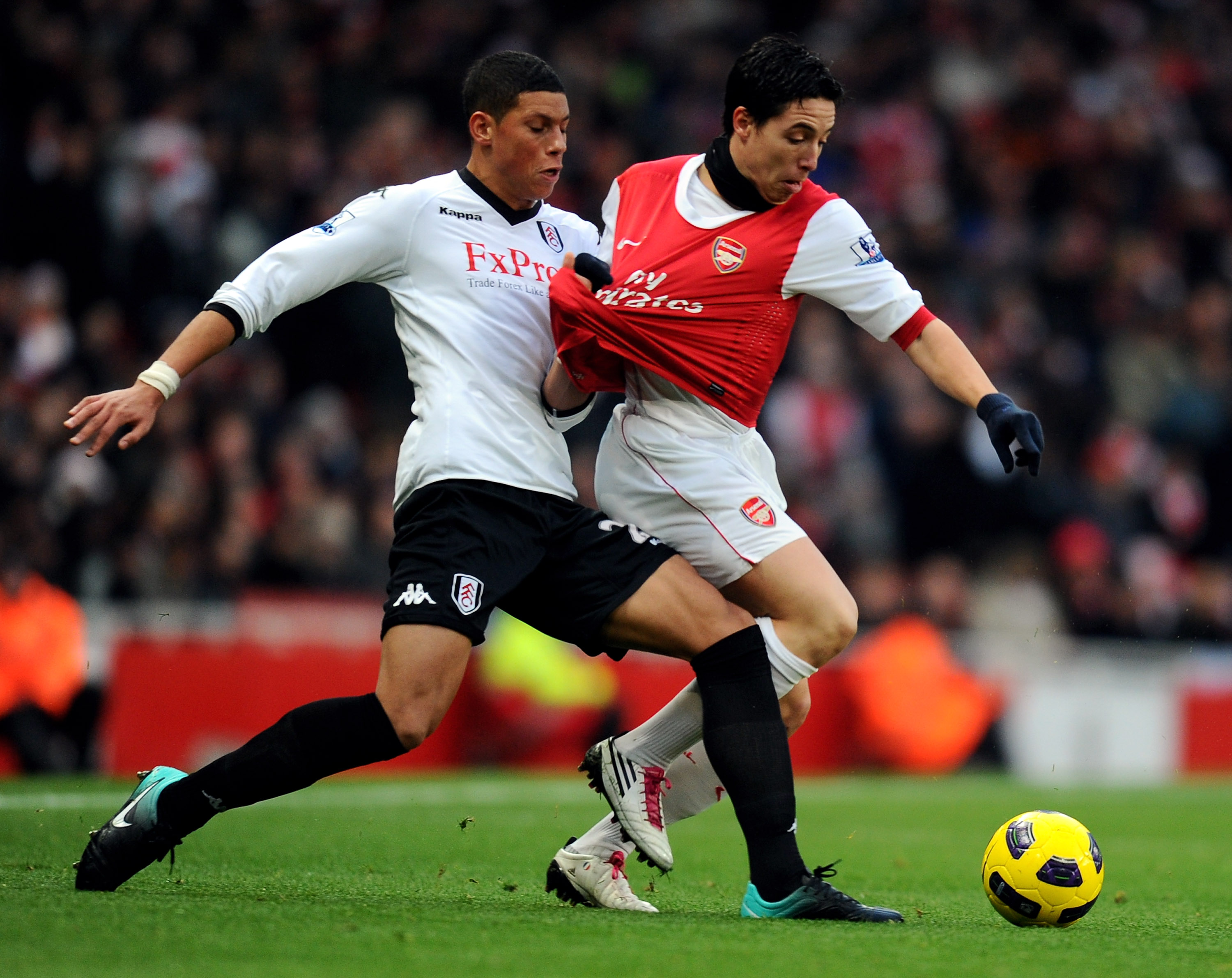 LONDON, ENGLAND - DECEMBER 04:  Samir Nasri of Arsenal (R) is tackled by Matthew Briggs of Fulham during the Barclays Premier League match between Arsenal and Fulham at the Emirates Stadium on December 4, 2010 in London, England.  (Photo by Mike Hewitt/Ge