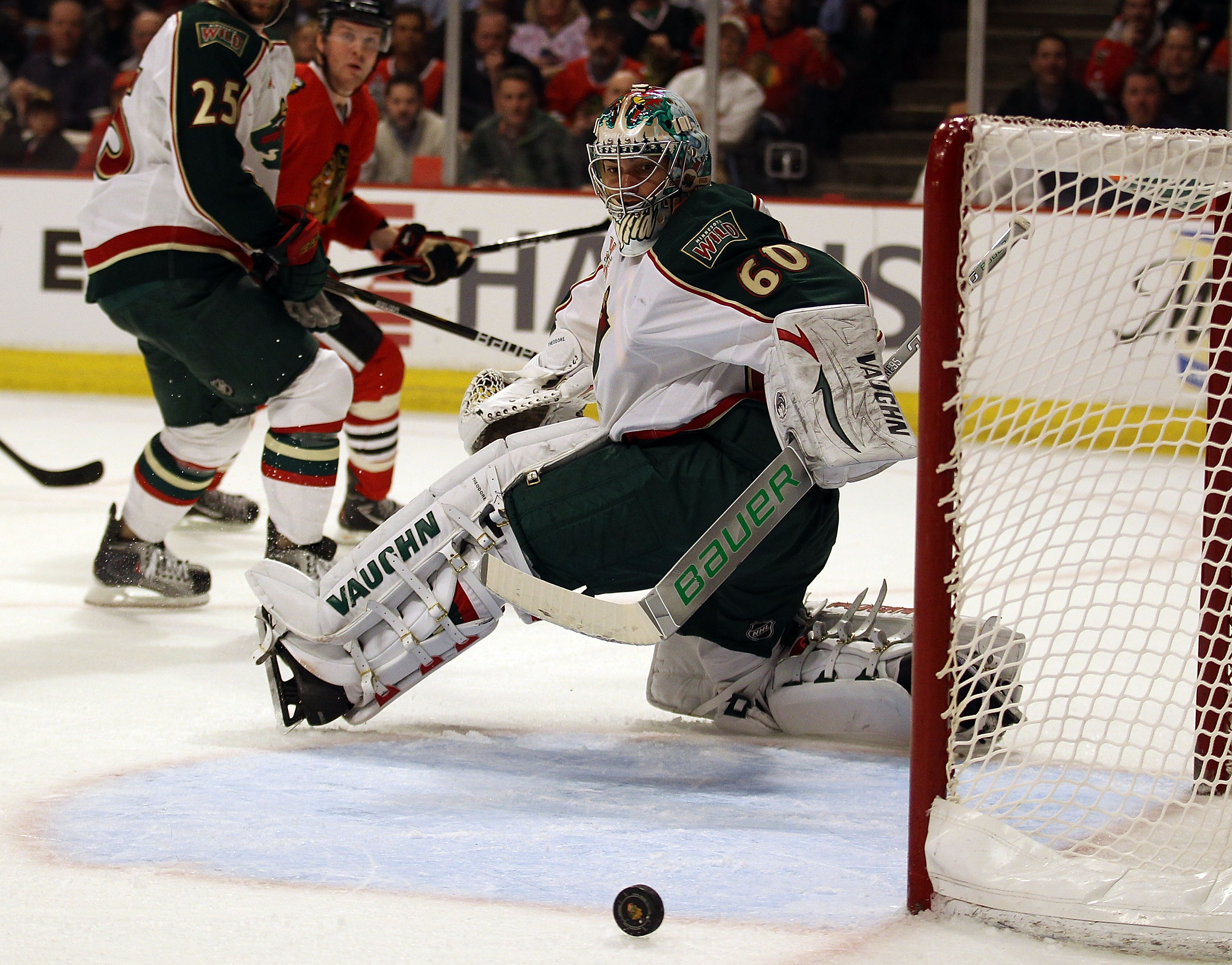 CHICAGO, IL - FEBRUARY 16: Jose Theodore #60 of the Minnesota Wild knocks the puck away for a save against the Chicago Blackhawks at the United Center on February 16, 2011 in Chicago, Illinois. The Blackhawks defeated the Wild 3-1. (Photo by Jonathan Dani