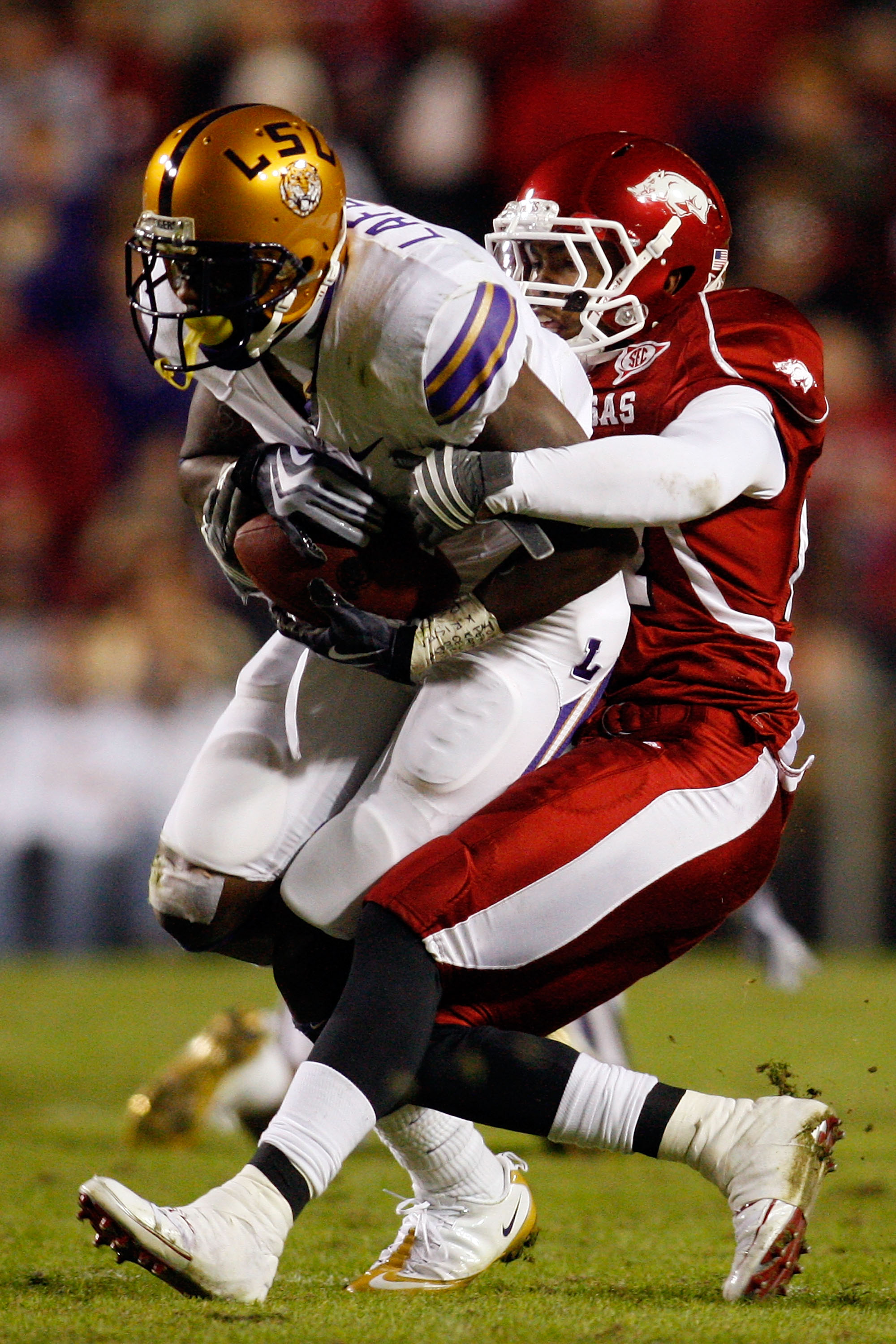 BATON ROUGE, LA - NOVEMBER 28:  Brandon LaFell #1 of the LSU Tigers is tackled by Jerell Norton #27 of the Arkansa Razorbacks at Tiger Stadium on November 28, 2009 in Baton Rouge, Louisiana.  The Tigers defeated the Razorbacks 33-30 in overtime.  (Photo b