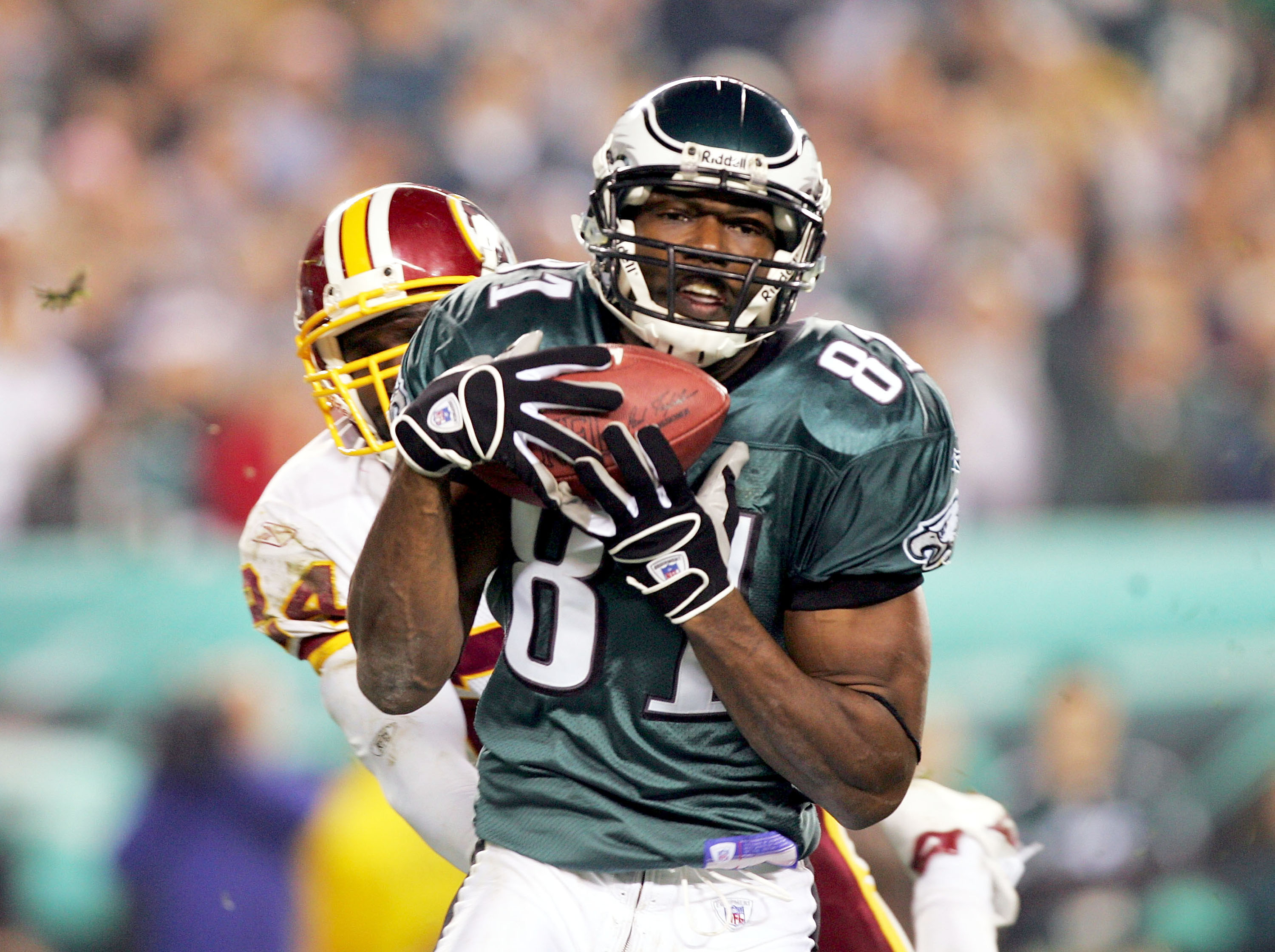 PHILADELPHIA - NOVEMBER 21:  Terrell Owens #81 of the Philadelphia Eagles catches the ball in front of Shawn Springs #24 of the Washington Redskins to score a touchdown in the third quarter at Lincoln Financial Field on November 21, 2004 in Philadelphia,