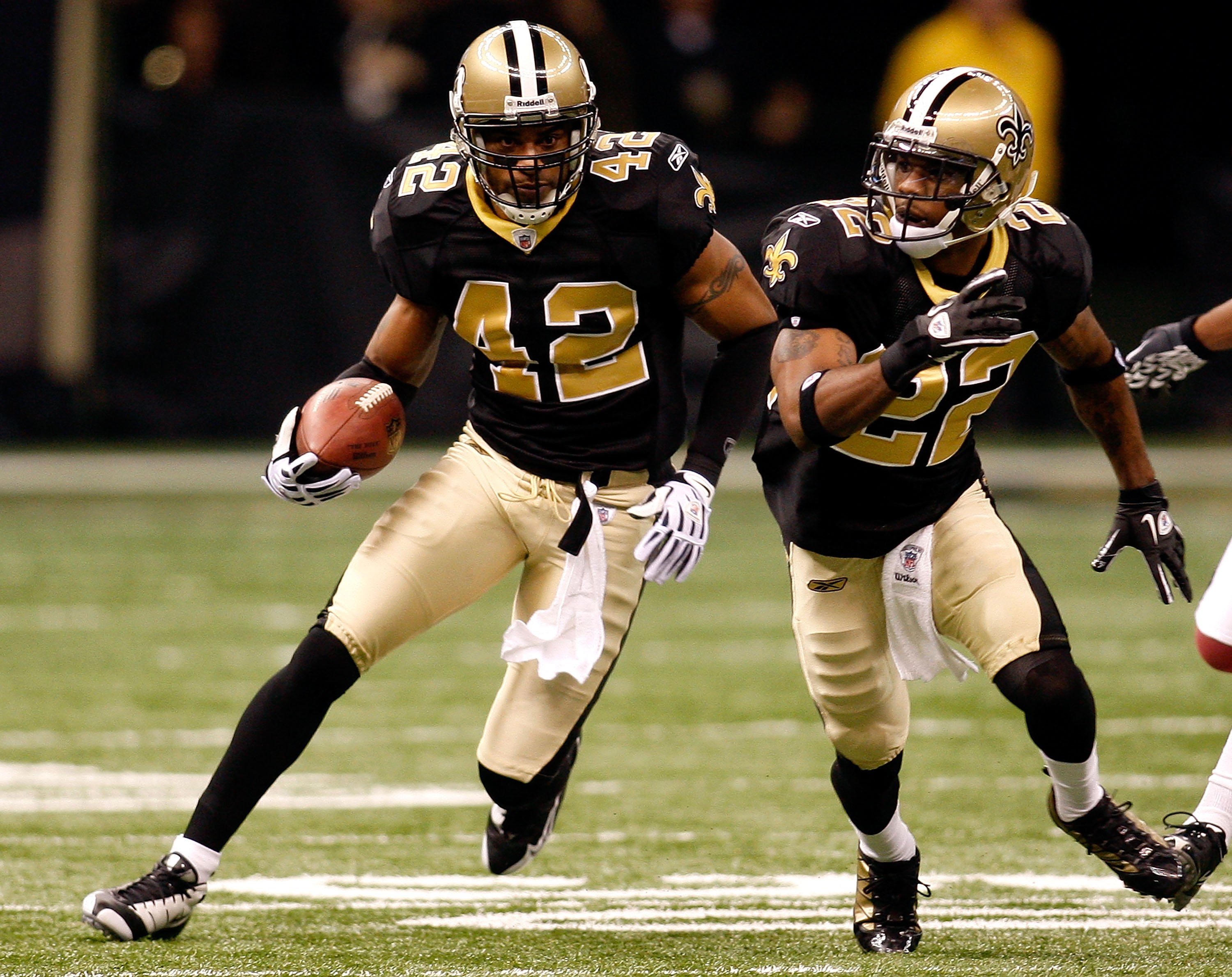 NEW ORLEANS - JANUARY 16:  Darren Sharper #42 of the New Orleans Saints returns a fumble recovery for positive yards as Tracy Porter #22 looks to block against the Arizona Cardinals during the NFC Divisional Playoff Game at Louisana Superdome on January 1
