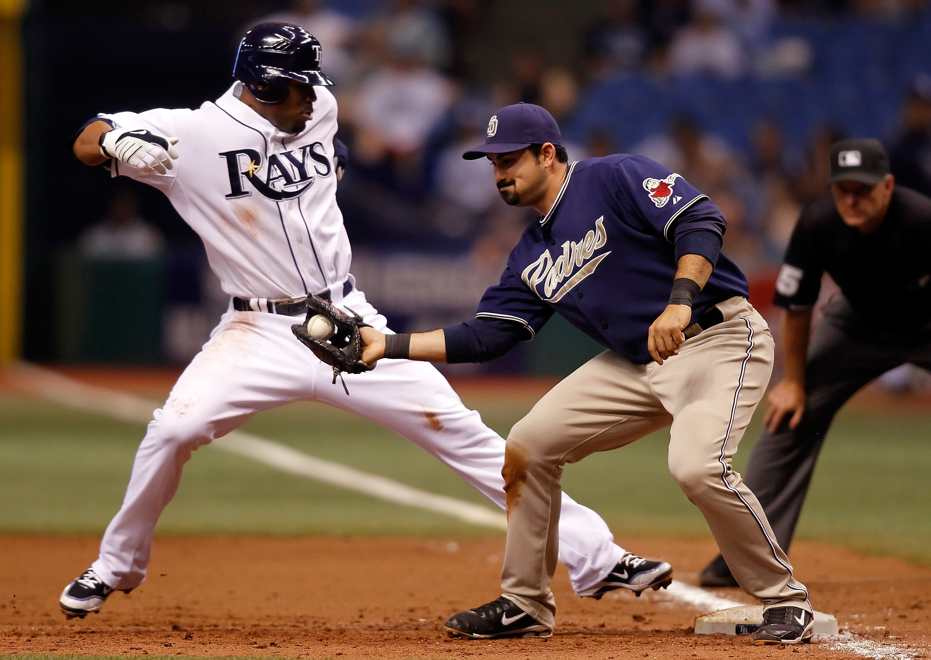 ST. PETERSBURG - JUNE 22:  Outfielder Carl Crawford #13 of the Tampa Bay Rays gets back to first safely as first baseman Adrian Gonzalez #23 of the San Diego Padres takes the throw during the game at Tropicana Field on June 22, 2010 in St. Petersburg, Flo
