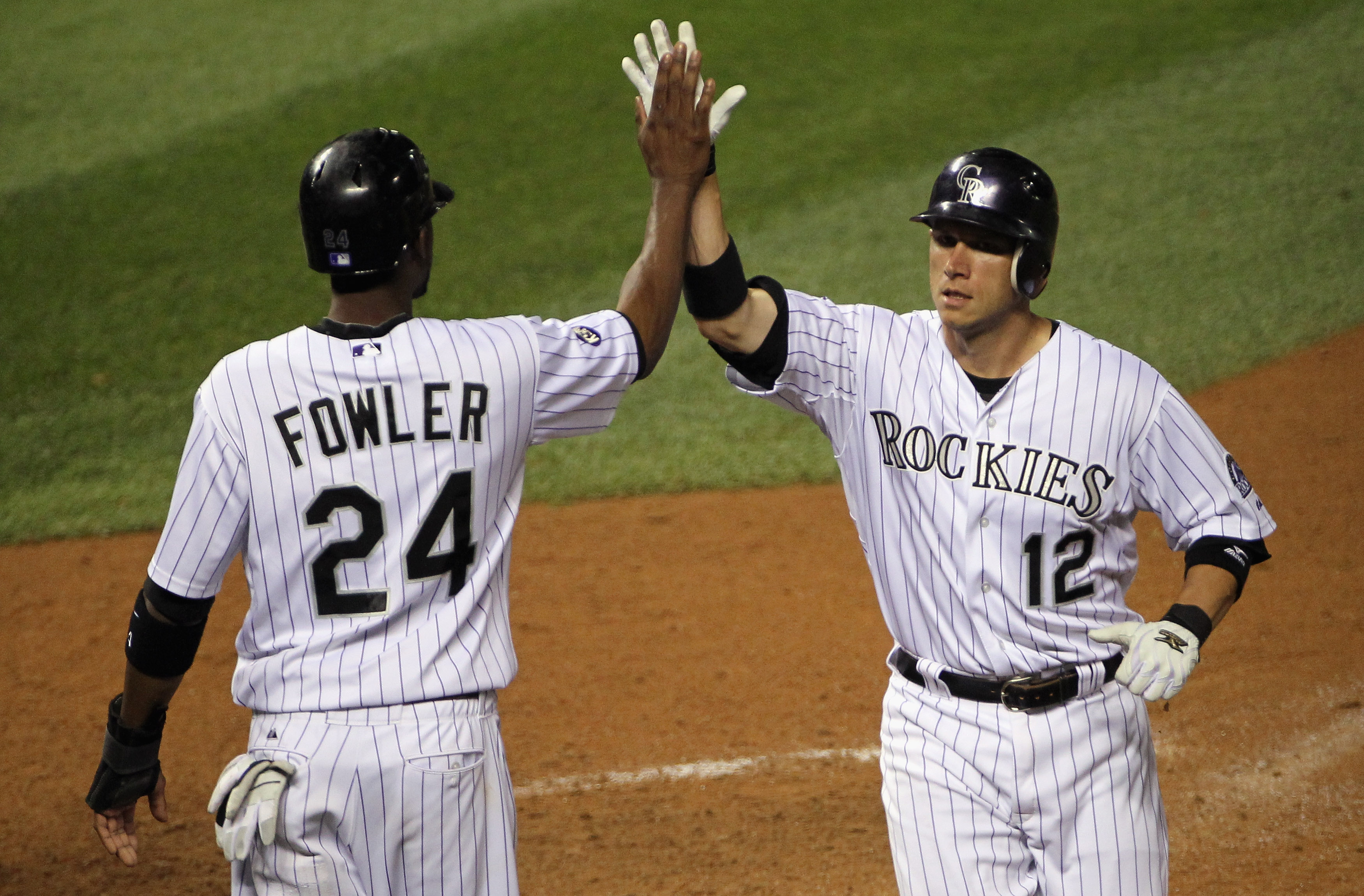 DENVER - SEPTEMBER 25:  Clint Barmes #12 and Dexter Fowler #24 of the Colorado Rockies celebrate after they scored on a double by Troy Tulowitzki to tie the score 9-9 with the San Francisco Giants in the eighth inning at Coors Field on September 25, 2010