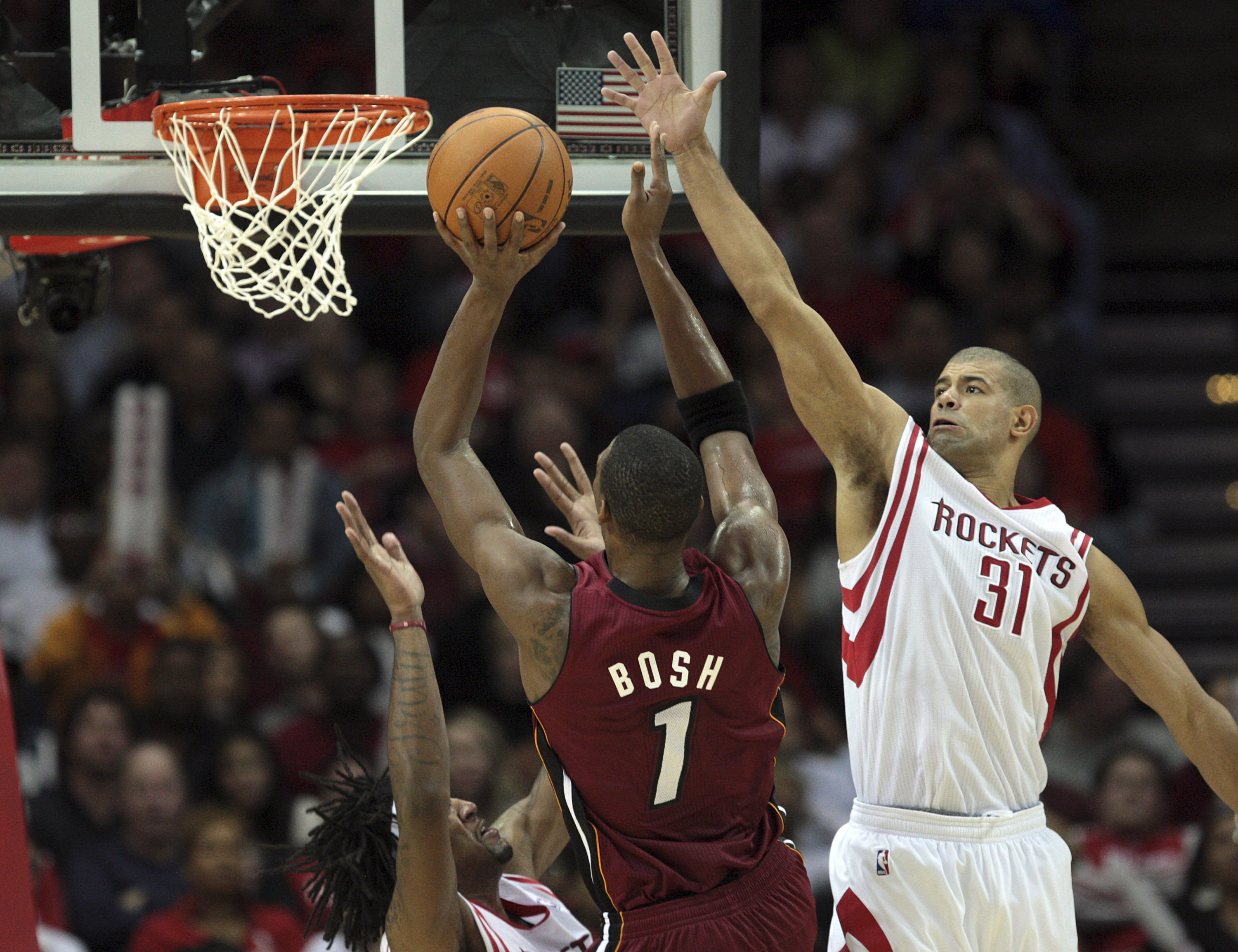 HOUSTON - DECEMBER 29: Chris Bosh #1 of the Miami Heat shoots over Shane Battier #31 of the Houston Rockets and Jordan Hill, left, in the fourth quarter at Toyota Center on December 29, 2010 in Houston, Texas. Miami won 125-119. NOTE TO USER: User express