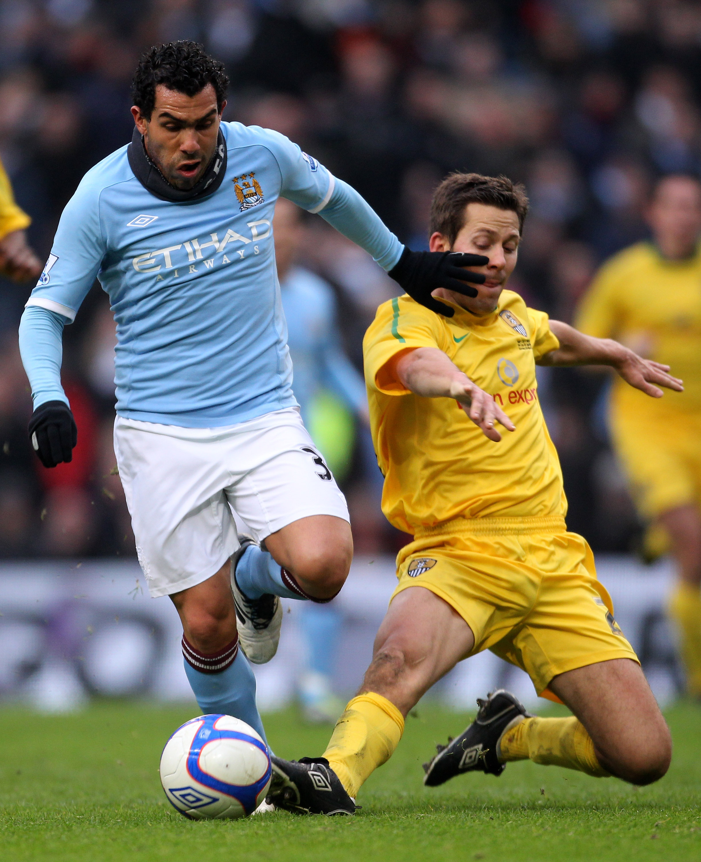 MANCHESTER, ENGLAND - FEBRUARY 20:  Carlos Tevez of Manchester City goes through on goal past Jon Harley of Nott County to score the third goal during the FA Cup sponsored by E.On 4th Round replay match between Manchester City and Notts County at City of