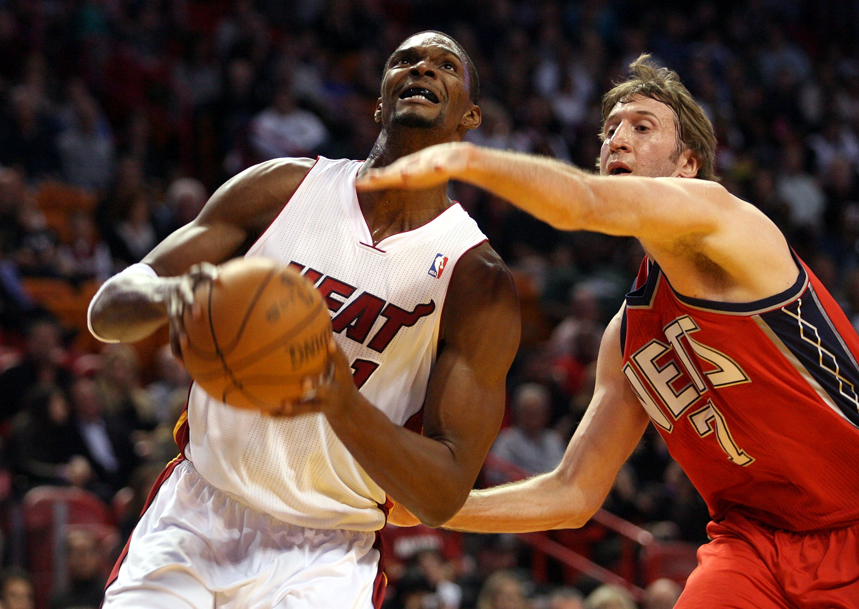MIAMI - NOVEMBER 06:  Forward Chris Bosh #1 of the Miami Heat drives against center Troy Murphy #7 of the New Jersey Nets  at American Airlines Arena on November 6, 2010 in Miami, Florida. NOTE TO USER: User expressly acknowledges and agrees that, by down