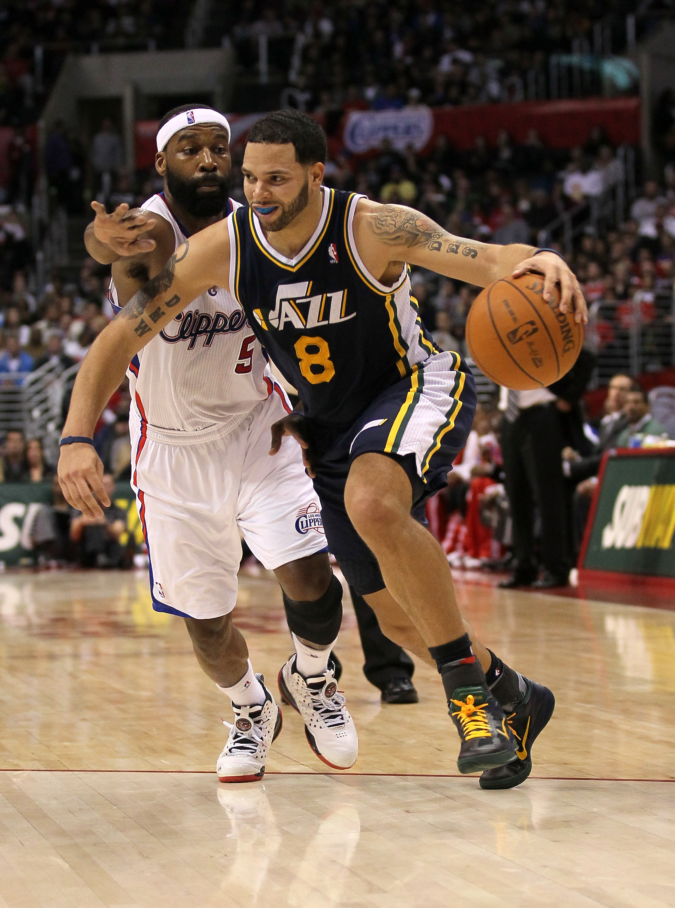 LOS ANGELES, CA - DECEMBER 29:  Deron Williams #8 of the Utah Jazz drives past Baron Davis #5 of the Los Angeles Clippers at Staples Center on December 29, 2010 in Los Angeles, California.   The Jazz won 103-85.  NOTE TO USER: User expressly acknowledges